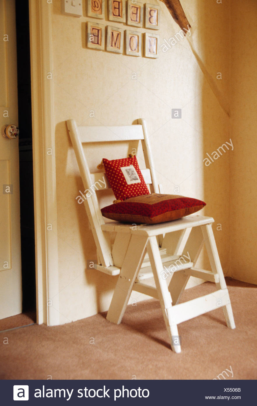 Close Up Of Cream Painted Folding Chair With Dark Red Cushions