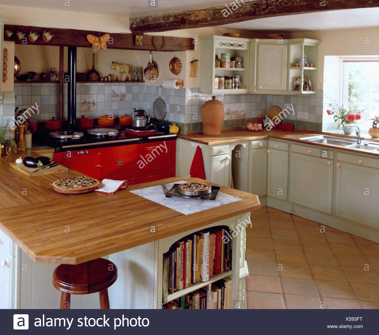 Island unit with wooden worktop in traditional country kitchen with red Aga double oven and terracotta floor tiles & Island unit with wooden worktop in traditional country kitchen with ...
