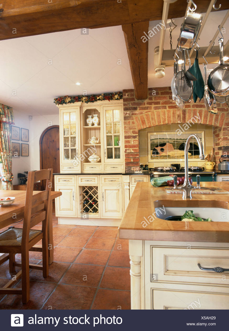 Terracotta Floor Tiles And Exposed Brick Wall In Country Kitchen