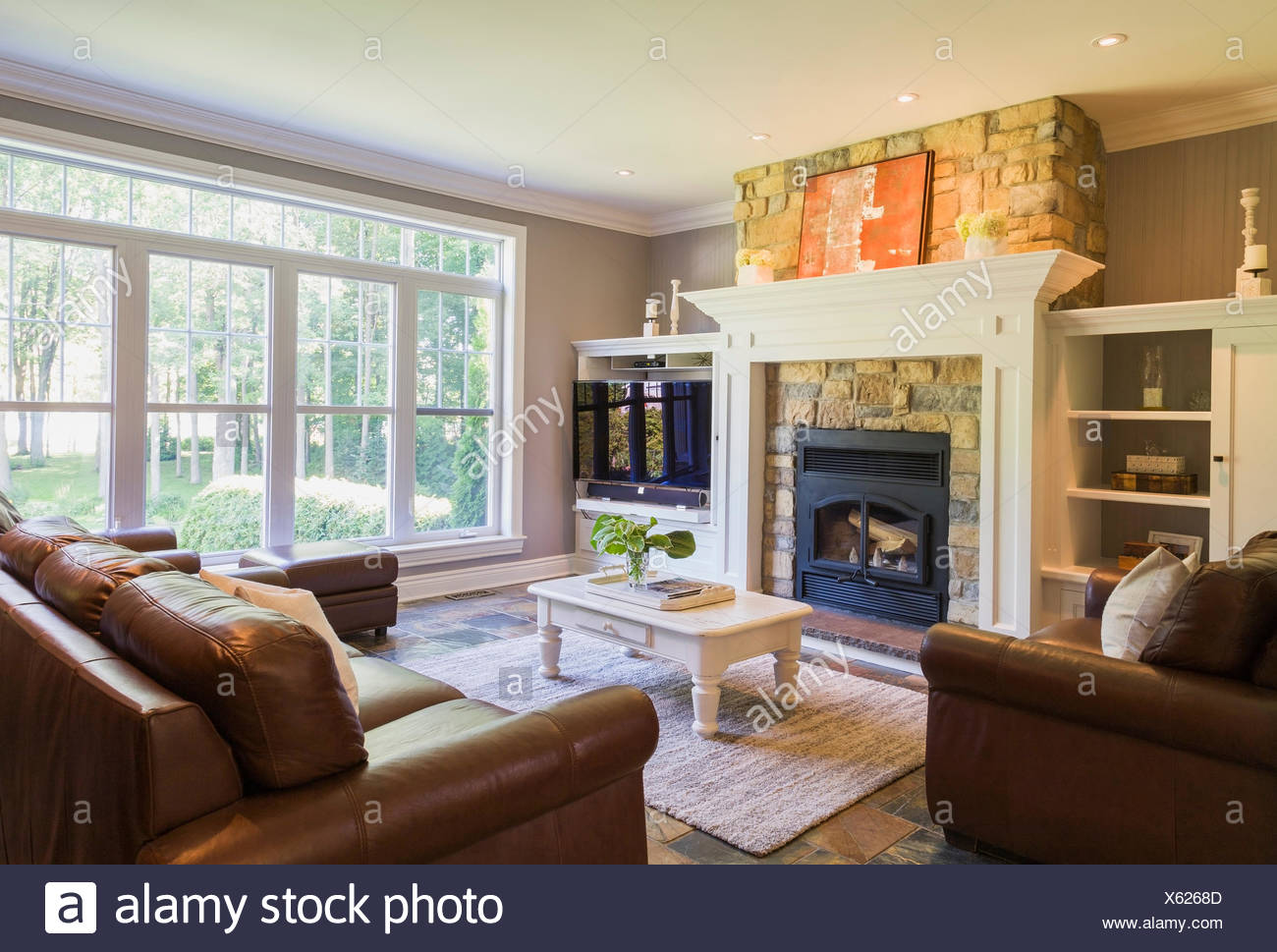 Brown leather sofa sitting chairs and natural stone fireplace in the living room inside a cottage style home quebec canada