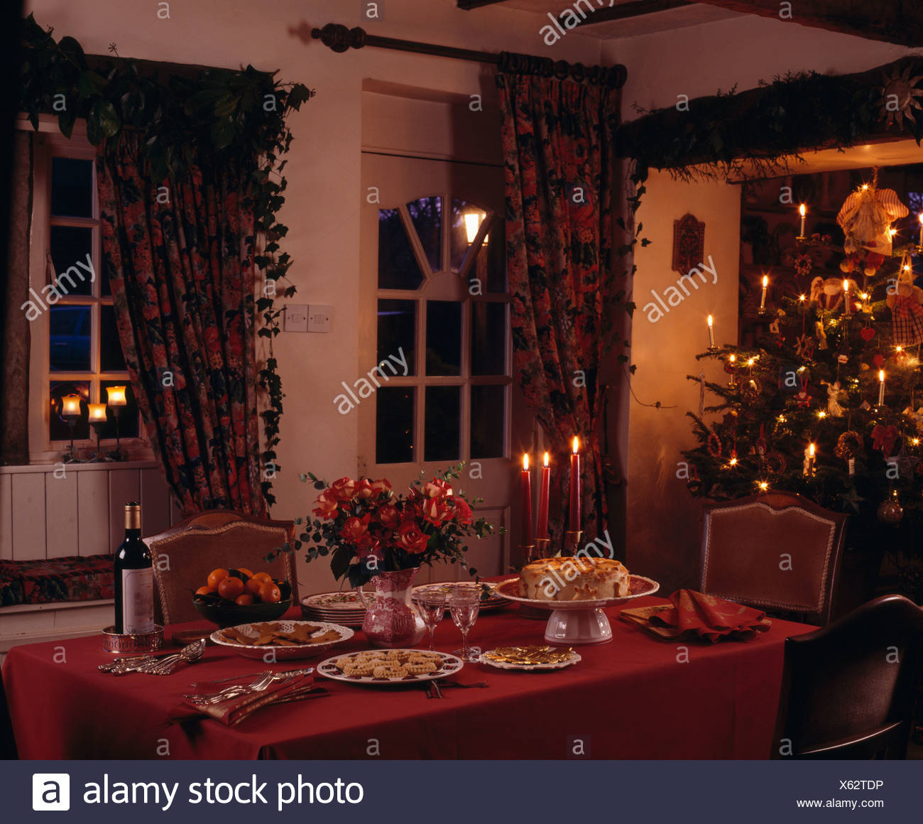 red cloth on table set for christmas tea in cottage dining room with fairy lights on christmas tree and heavy curtains on window