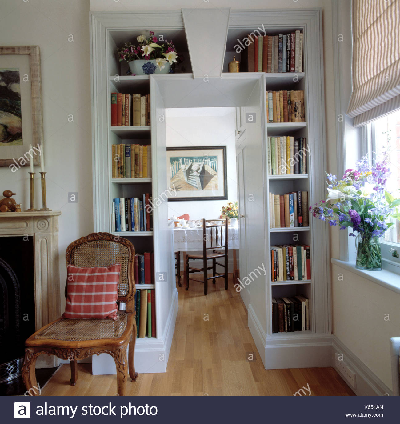 Antique Bergere Chair Beside Bookshelves Framing Doorway In Apartment Dining  Room With Wooden Flooring