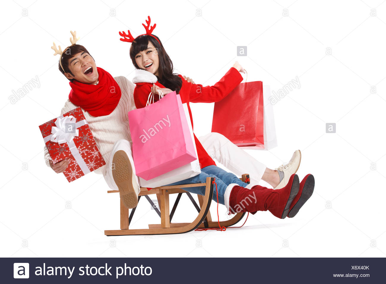 young couple holding christmas gifts on sled