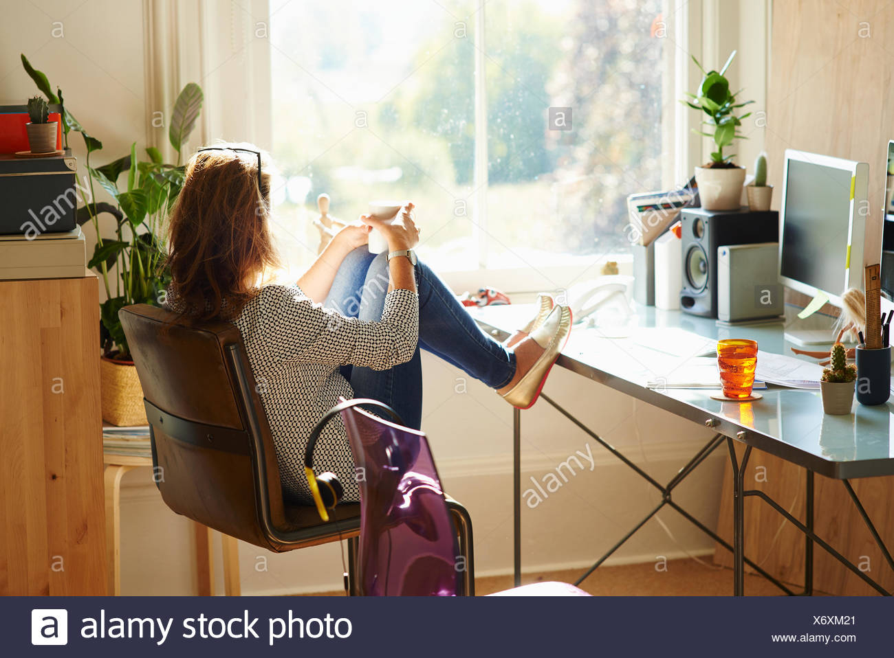 sunny day home office. Pensive Woman Looking Through Window With Feet Up On Desk In Sunny Home Office - Stock Day O