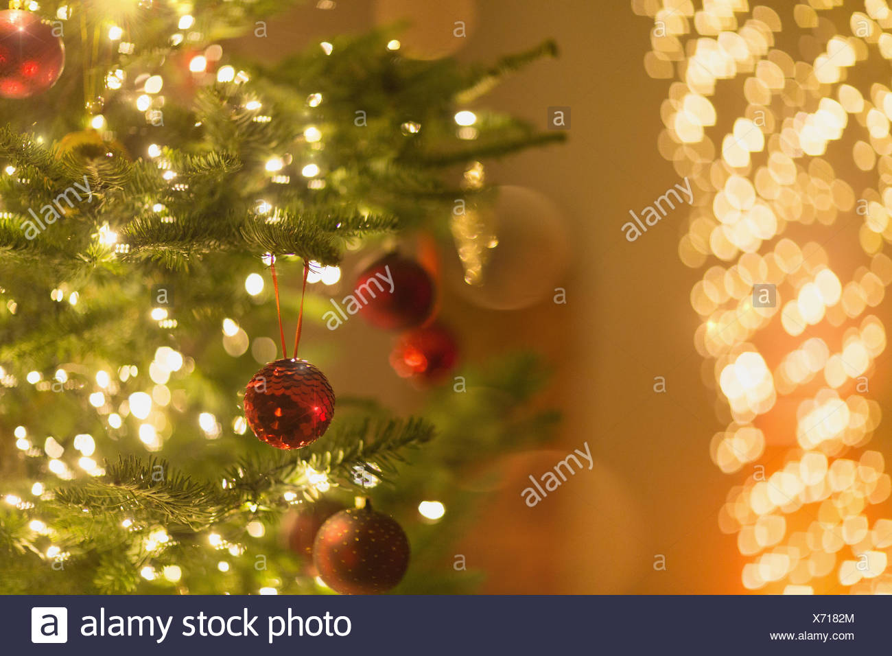 red ornaments hanging from christmas tree with string lights - How To String Lights On A Christmas Tree