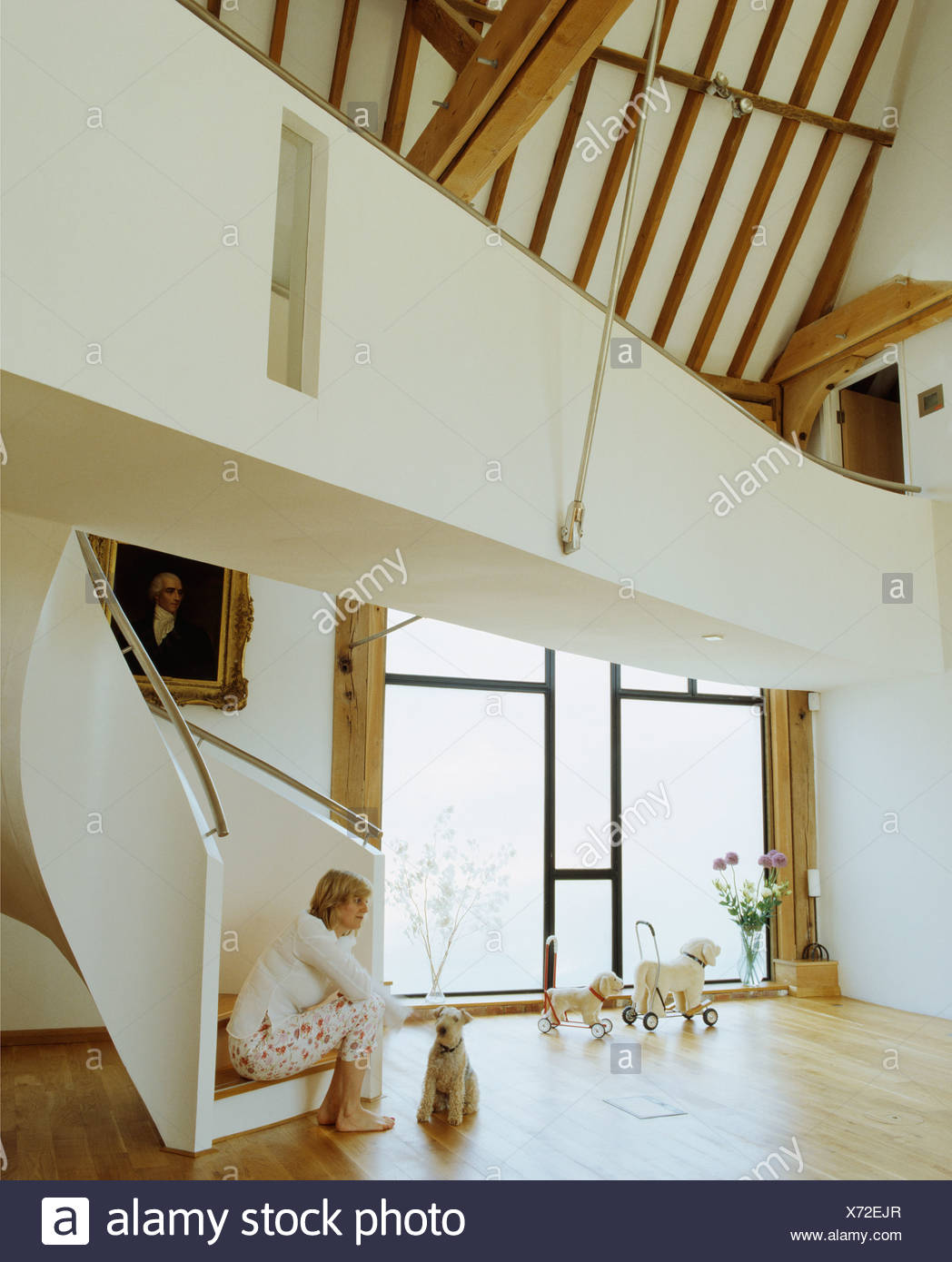 Woman Sitting On Staircase With Dog In Hall In Modern Country Barn  Conversion With Gallery Landing