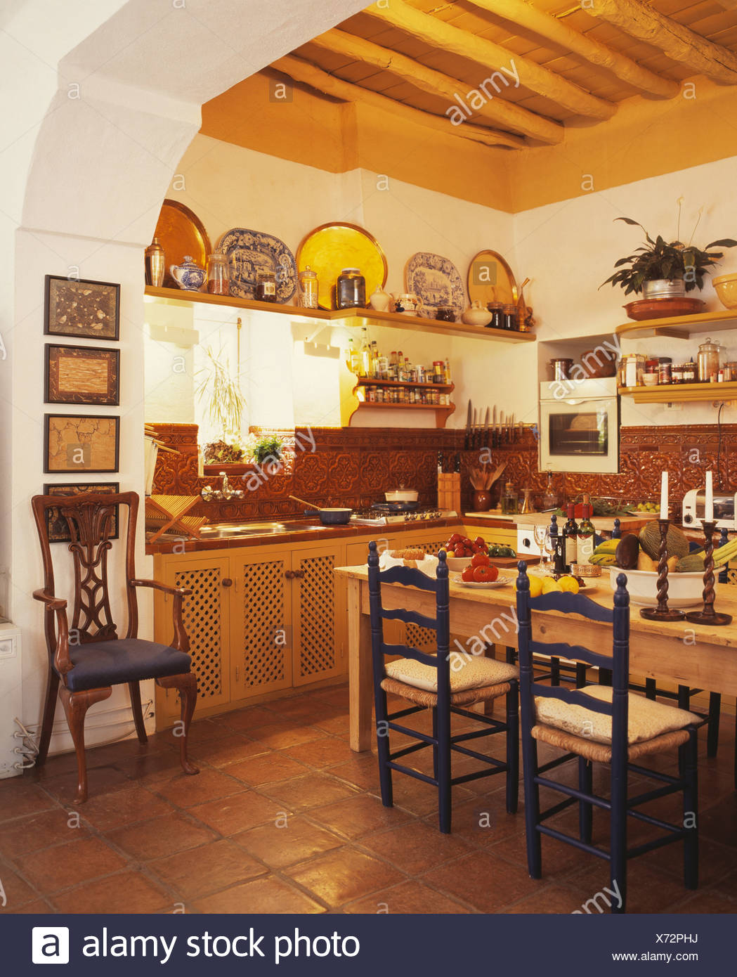 Ladderback chairs at wooden table in Spanish country kitchen with quarry tiled floor and beamed ceiling & Ladderback chairs at wooden table in Spanish country kitchen with ...