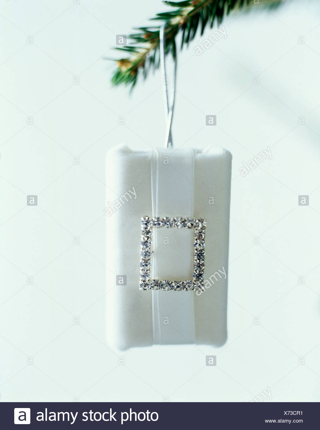Close-up of Christmas present gift-wrapped in white paper decorated ...