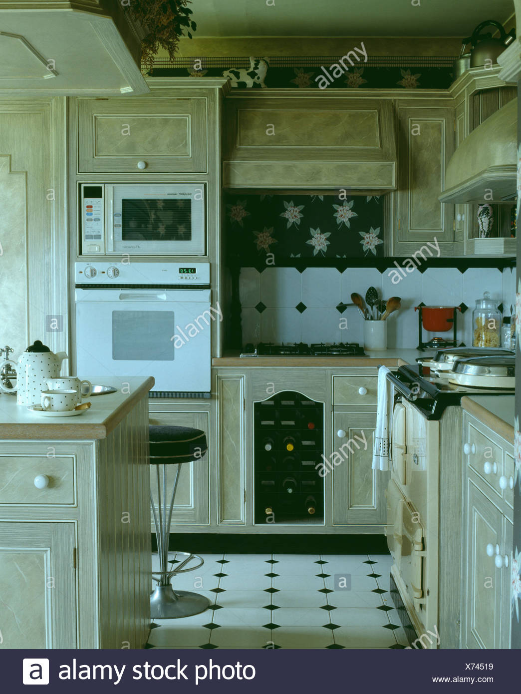 Eye-level microwave and white oven in kitchen with paint effect ...