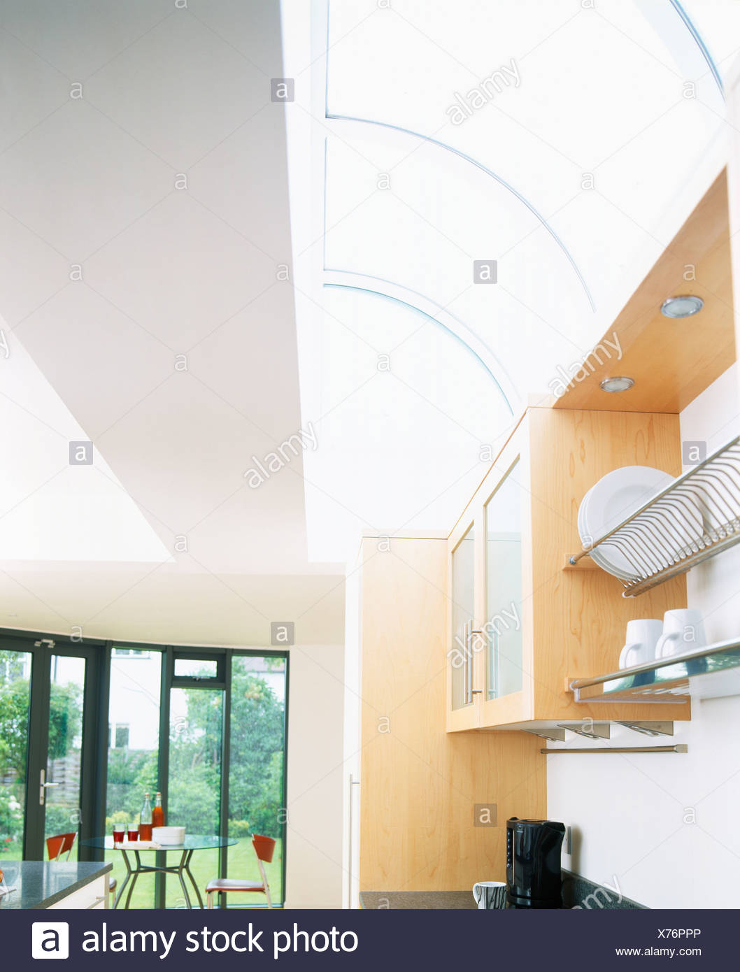 Curved Glass Ceiling In Large Modern Kitchen With View Of Garden