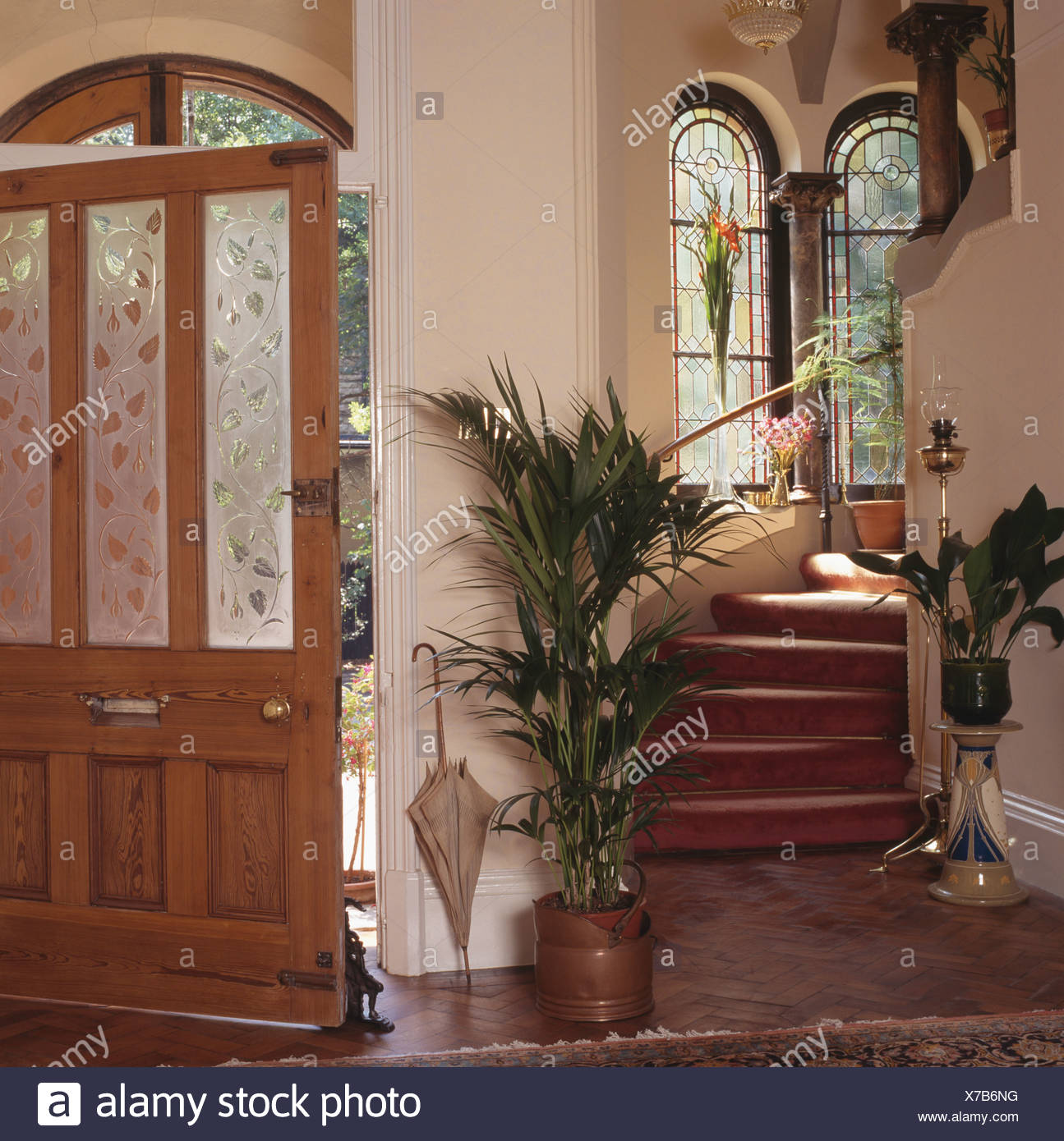 Green Houseplants On Either Side Of Staircase In Cream Hall With
