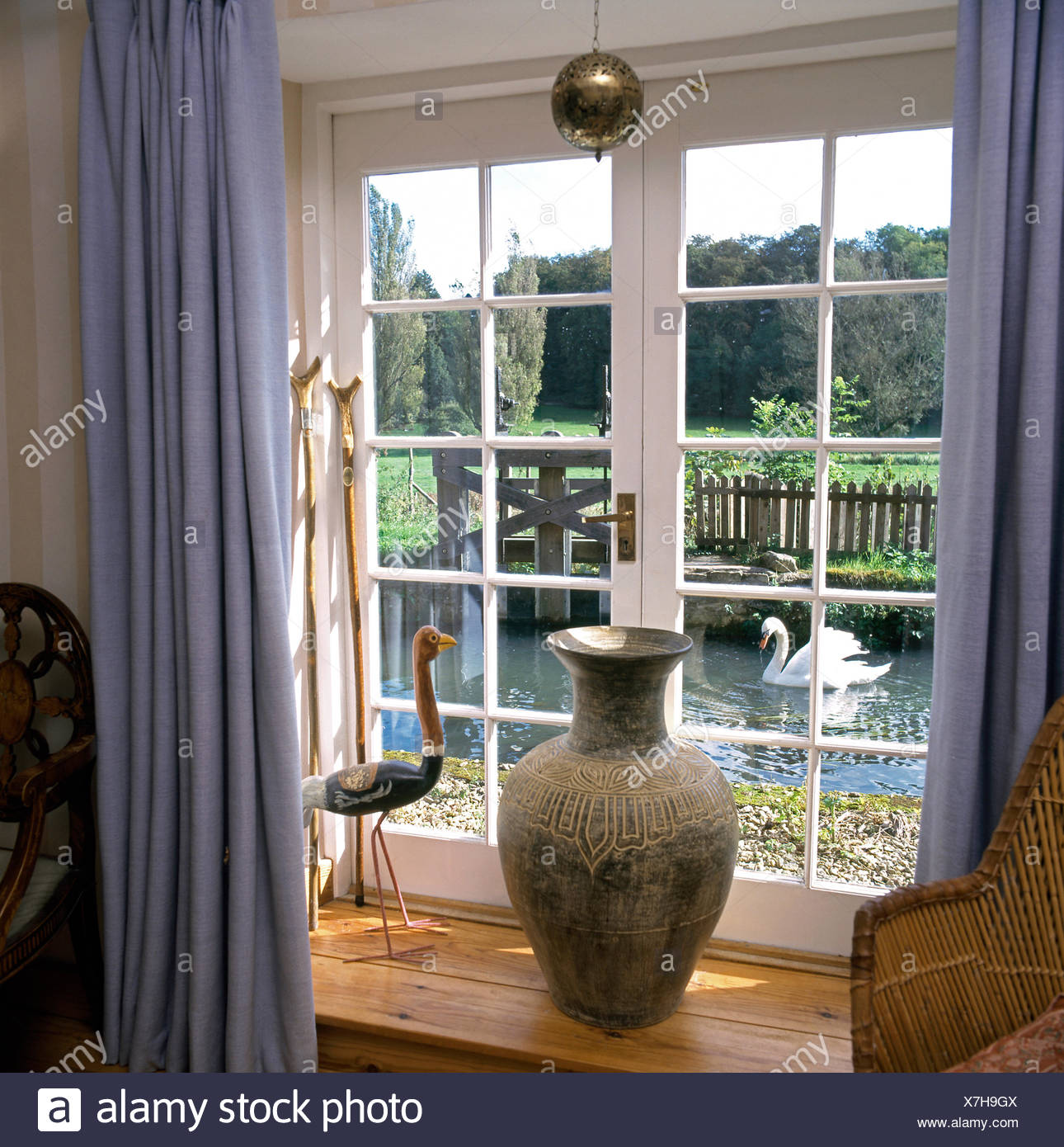Blue Curtains On Window With A Tall Pot And A Wooden Bird In Country Dining  Room