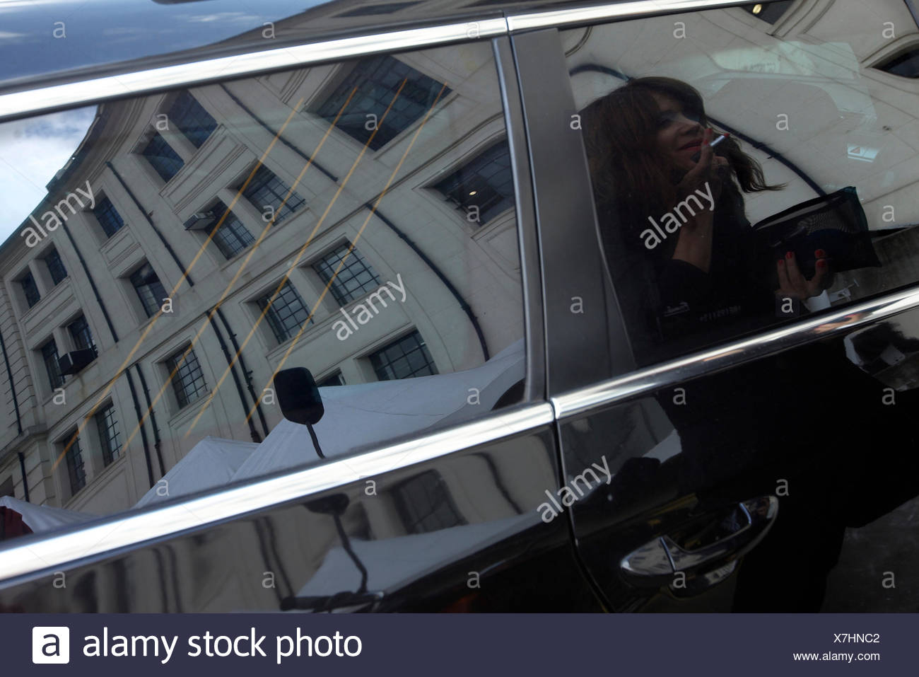 A Businesswoman Applies Lipstick Using The Reflection Of Her Car S