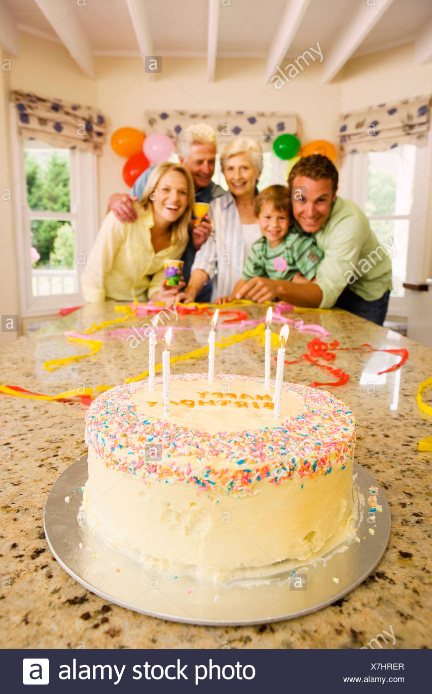 Three Generation Family Celebrating Birthday At Home Smiling
