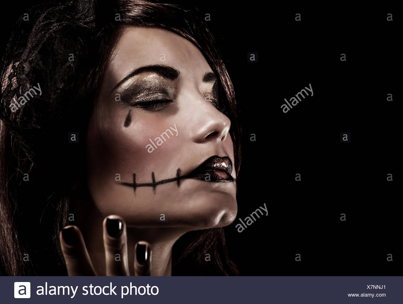 evil witch on black background, closeup portrait of young beautiful