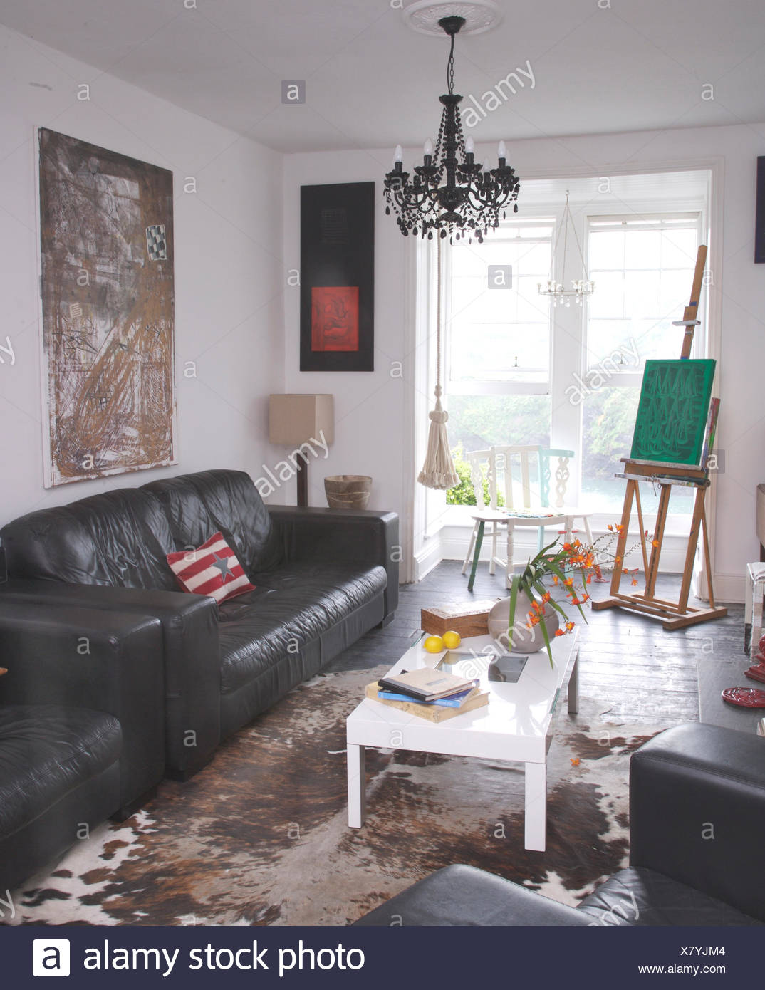 Black Leather Sofas And A White Coffee Table In Artistu0027s Coastal Living  Room With A Vintage Cow Hide Rug On Floor