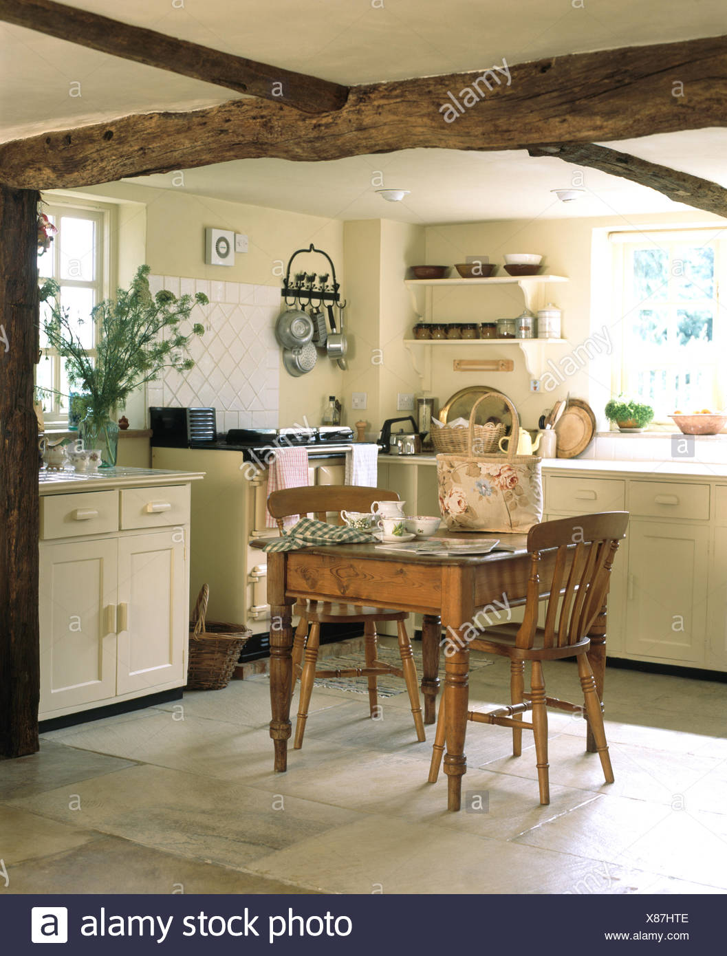 vintage pine dining table and chairs in a cream cottage kitchen with