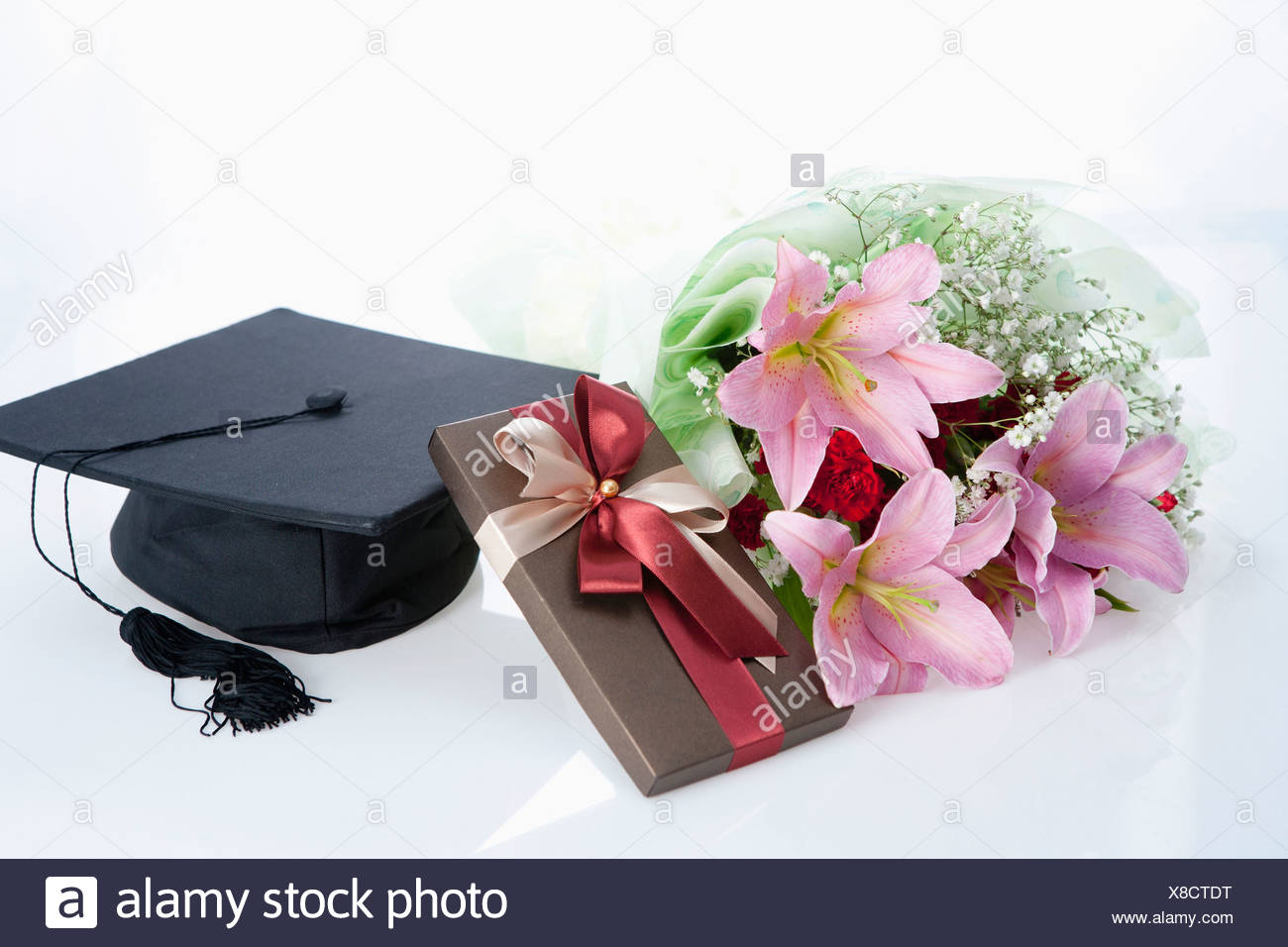The Bouquet Of Flower Gift And Graduation Cap Stock Photo