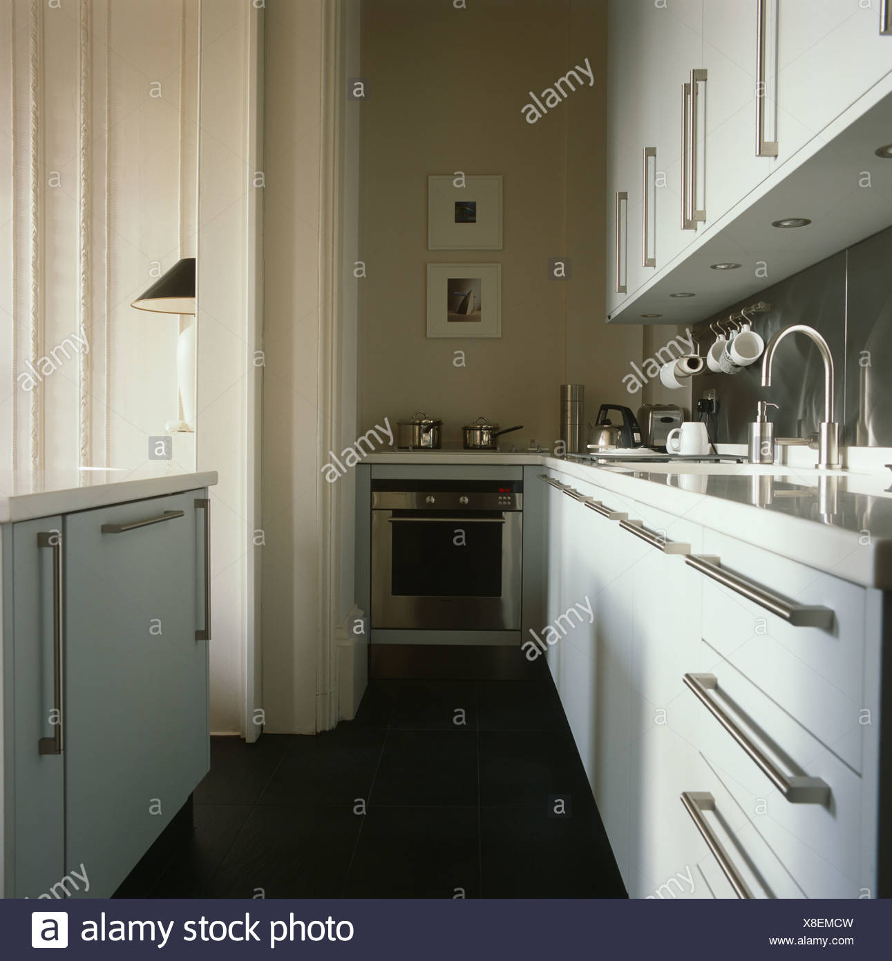 Brushed Steel Handles On White Cabinets In Galley Kitchen With Slate Flooring And Stainless Oven