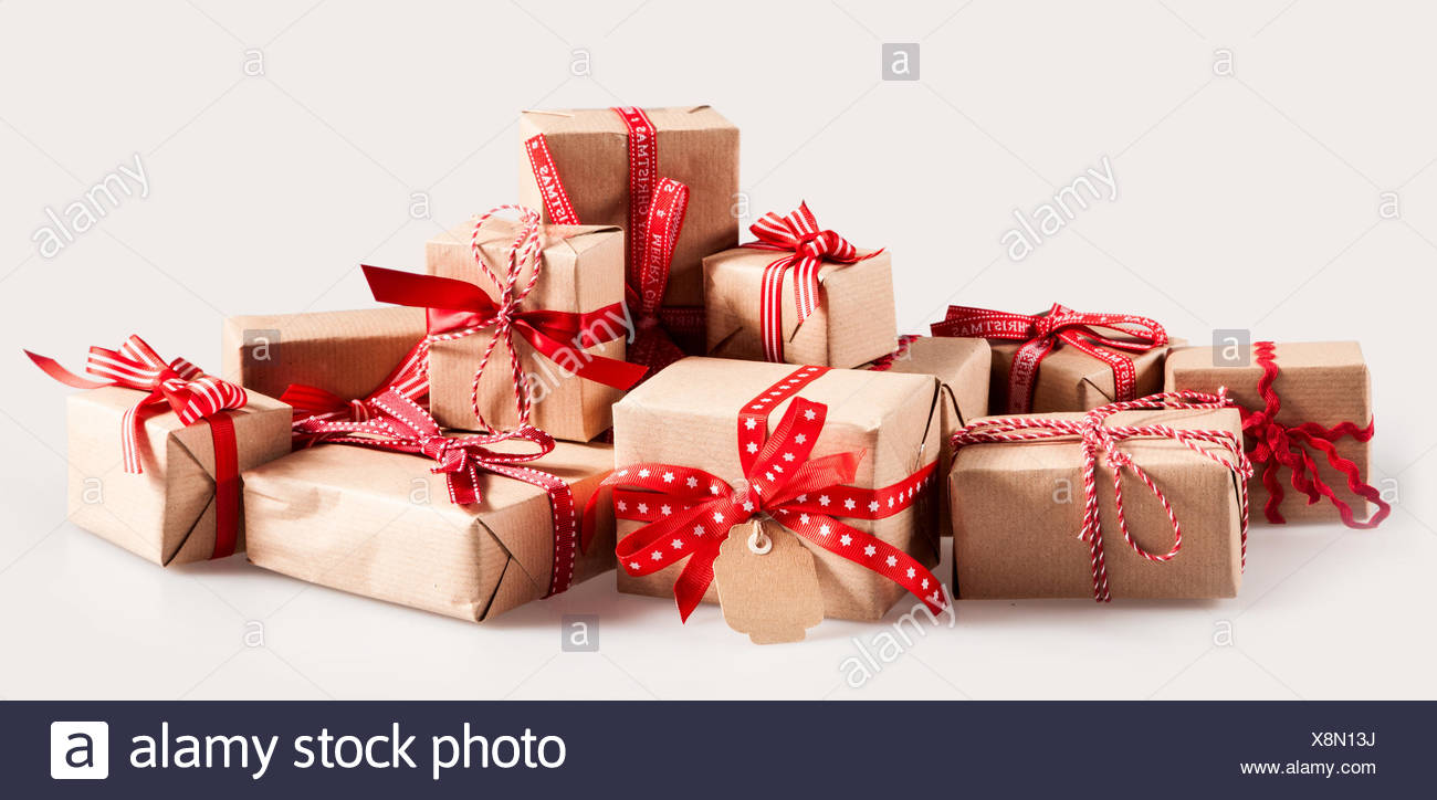 Pile of Christmas gifts with colorful red bows wrapped in brown ...