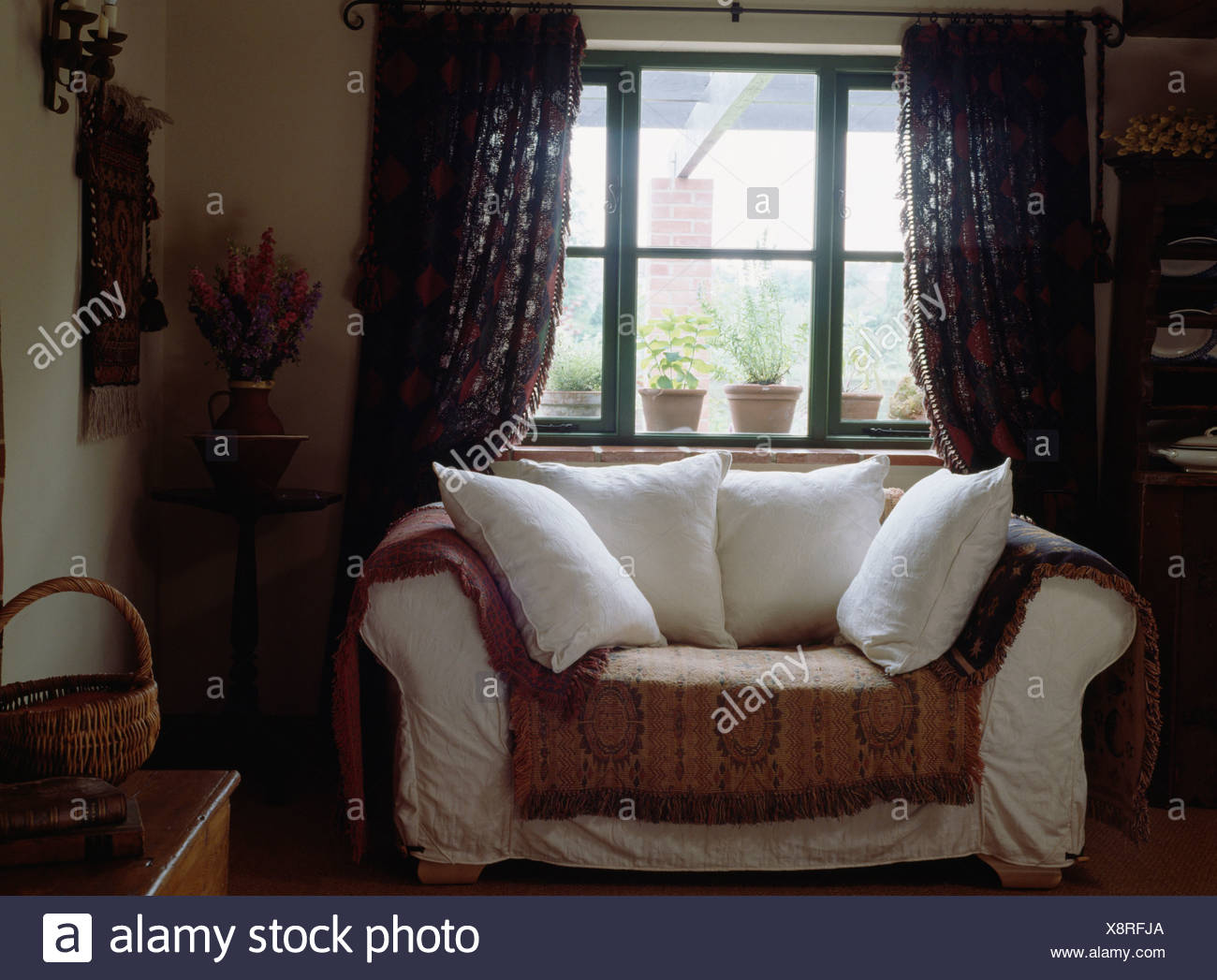 Ordinaire White Cushions On White Sofa With Patterned Throw In Front Of Window In Small  Cottage Living Room