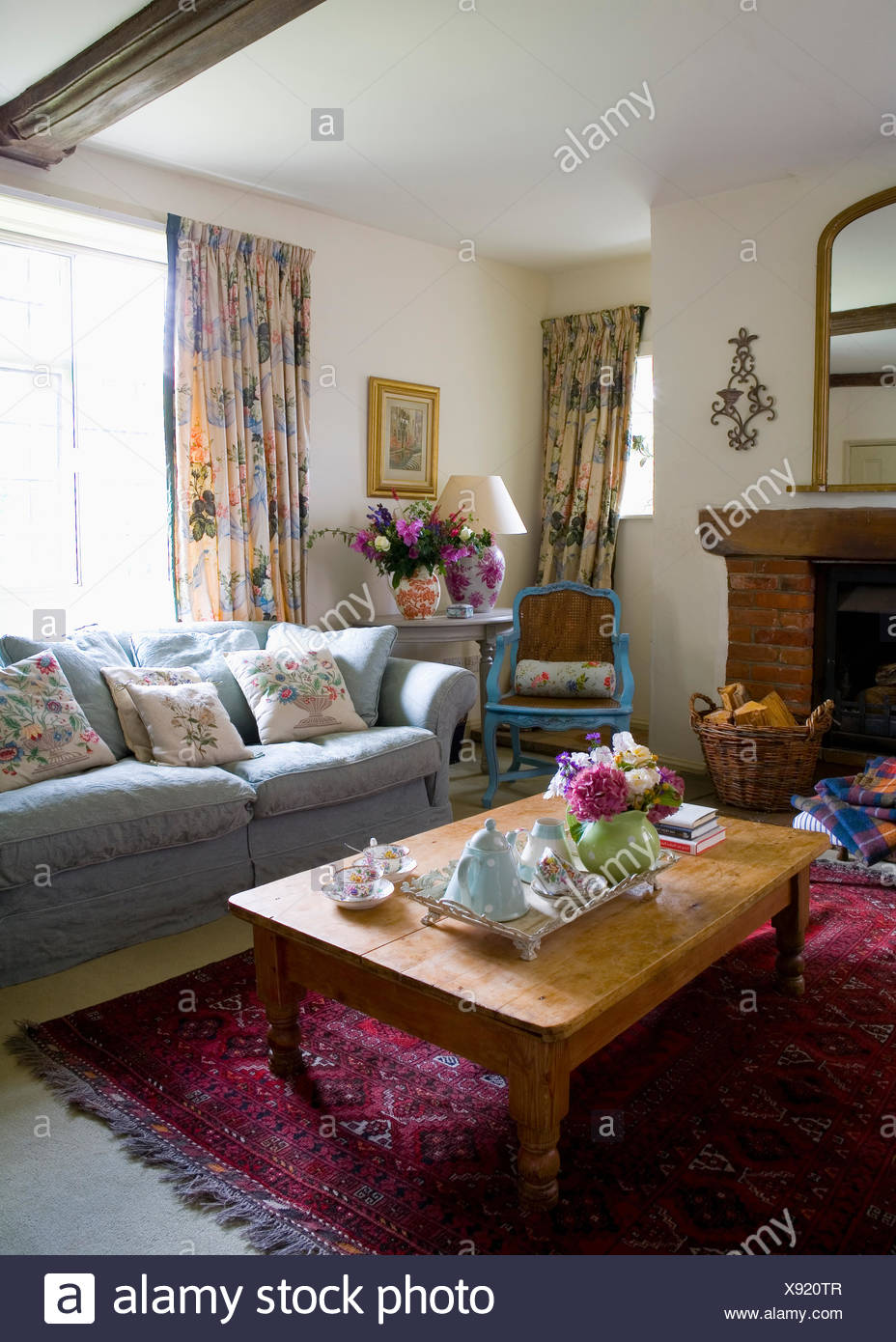 Genial Blue Sofa In Front Of Window With Floral Curtains In Country Living Room  With Vintage Tea Set On Pine Coffee Table