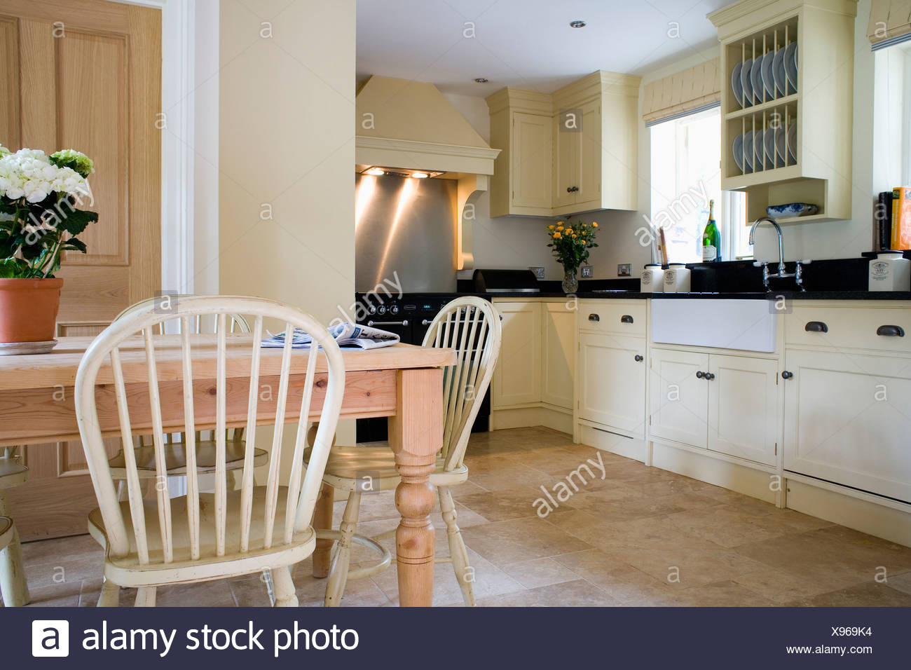 Ordinaire Pale Wood Windsor Chairs And Pine Table In Traditional Country Kitchen With  Cream Fitted Units And Travertine Tiled Floor