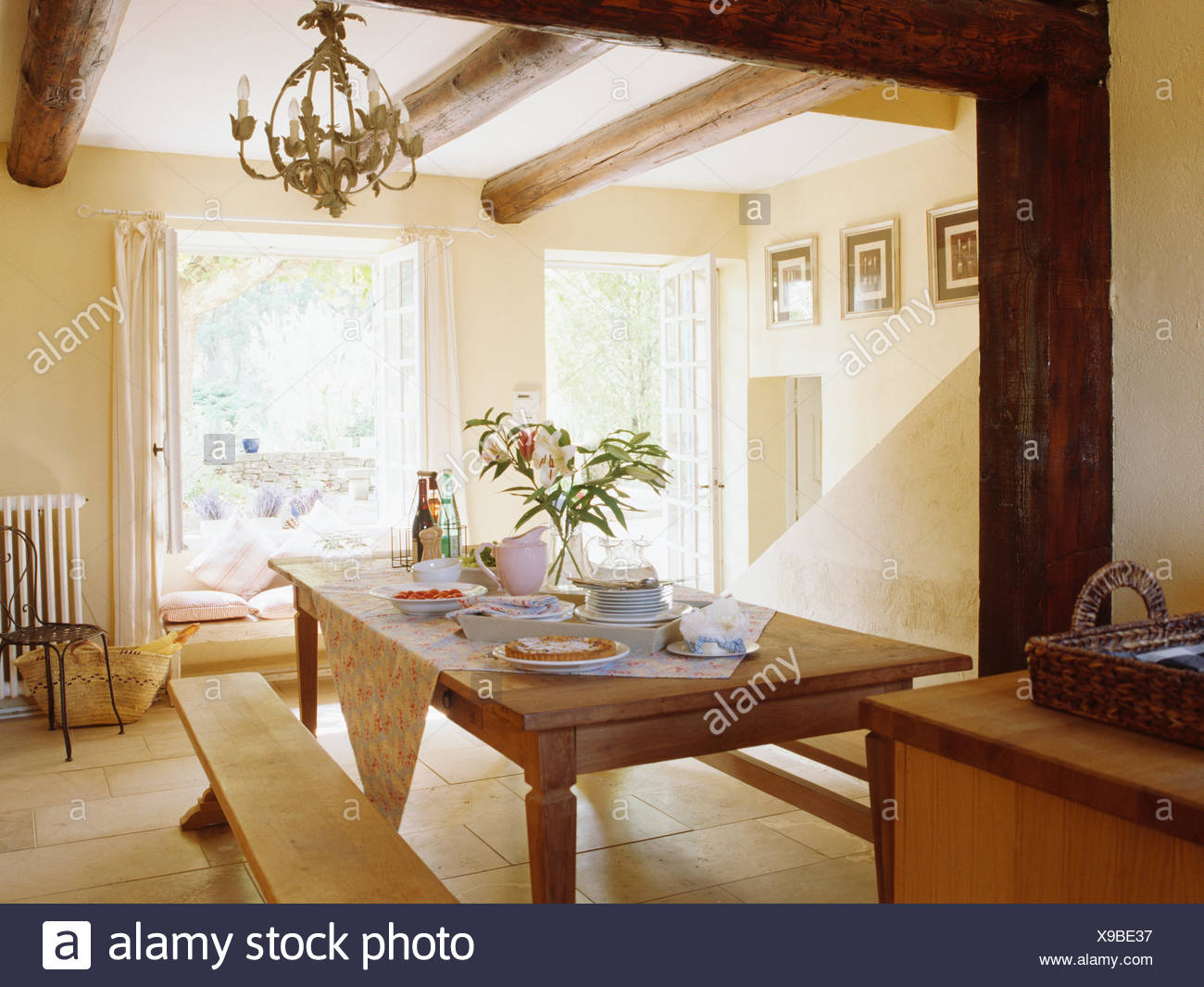 Simple Wooden Benches And Old Pine Table In Cream French Country Dining Room