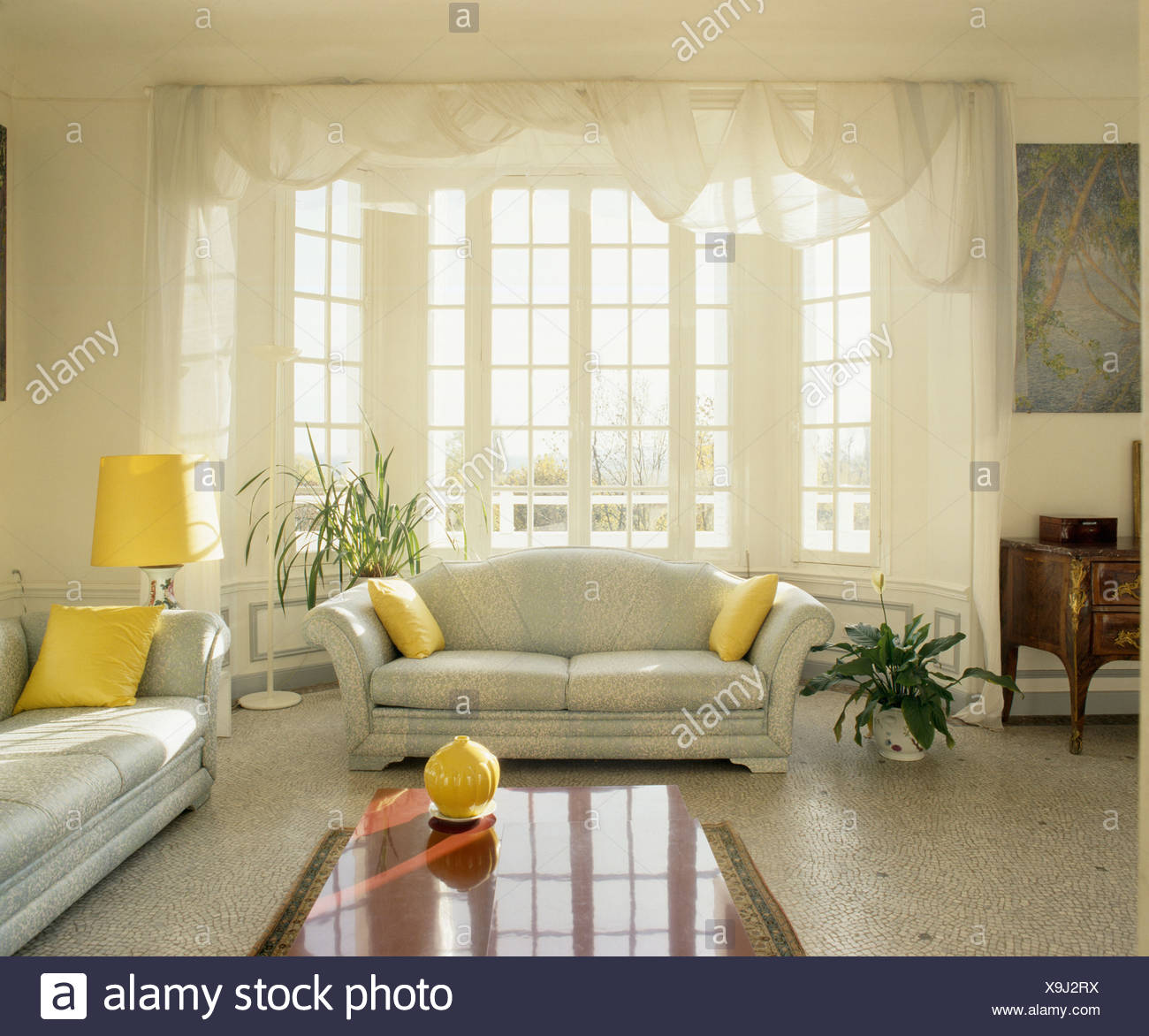 Terrazzo Floor And Grey Sofas With Yellow Cushions In Traditional French  Living Room With Voile Drapes On Bay Window