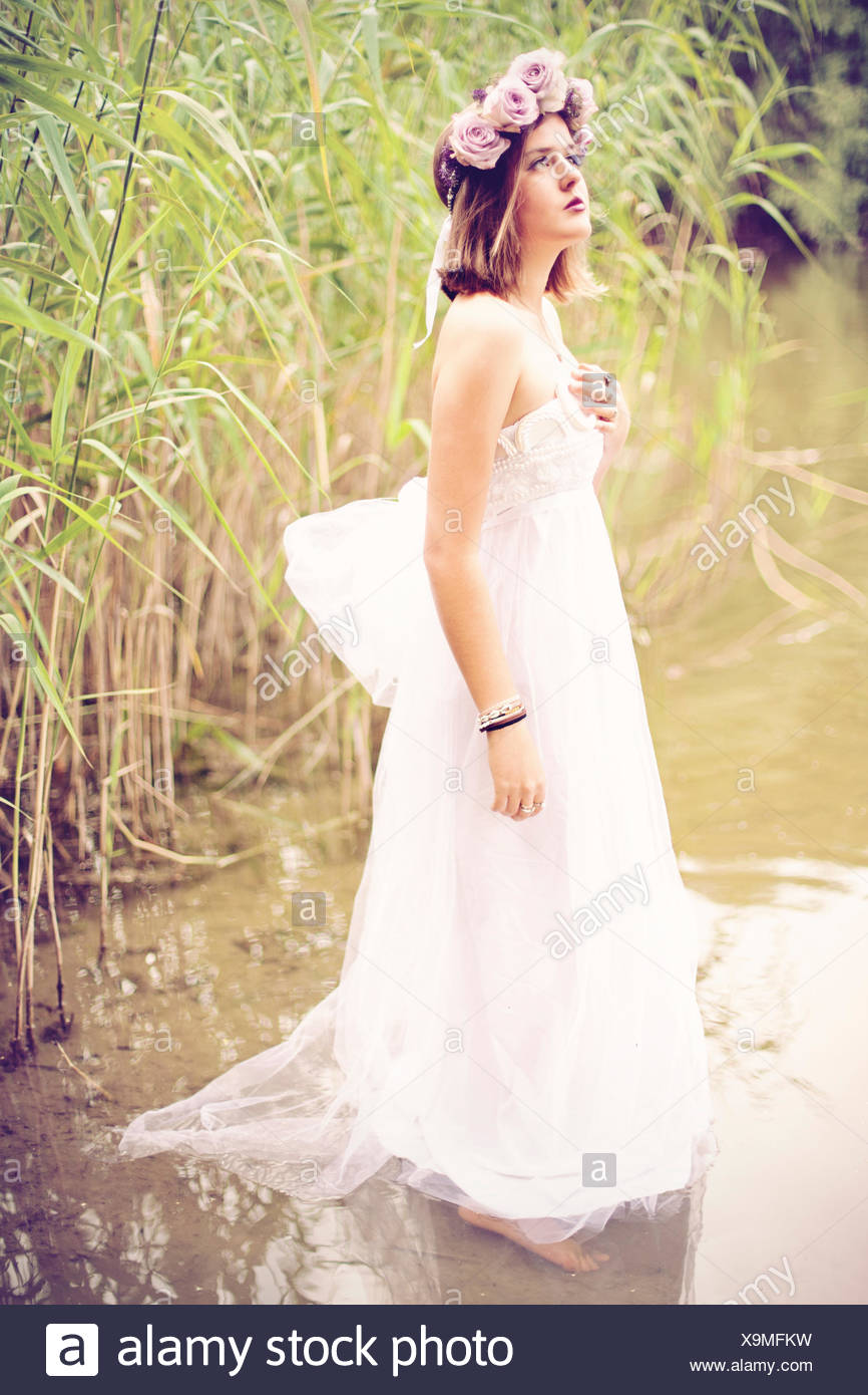 Woman Wearing Wedding Dress And Flower Crown Standing In The Water