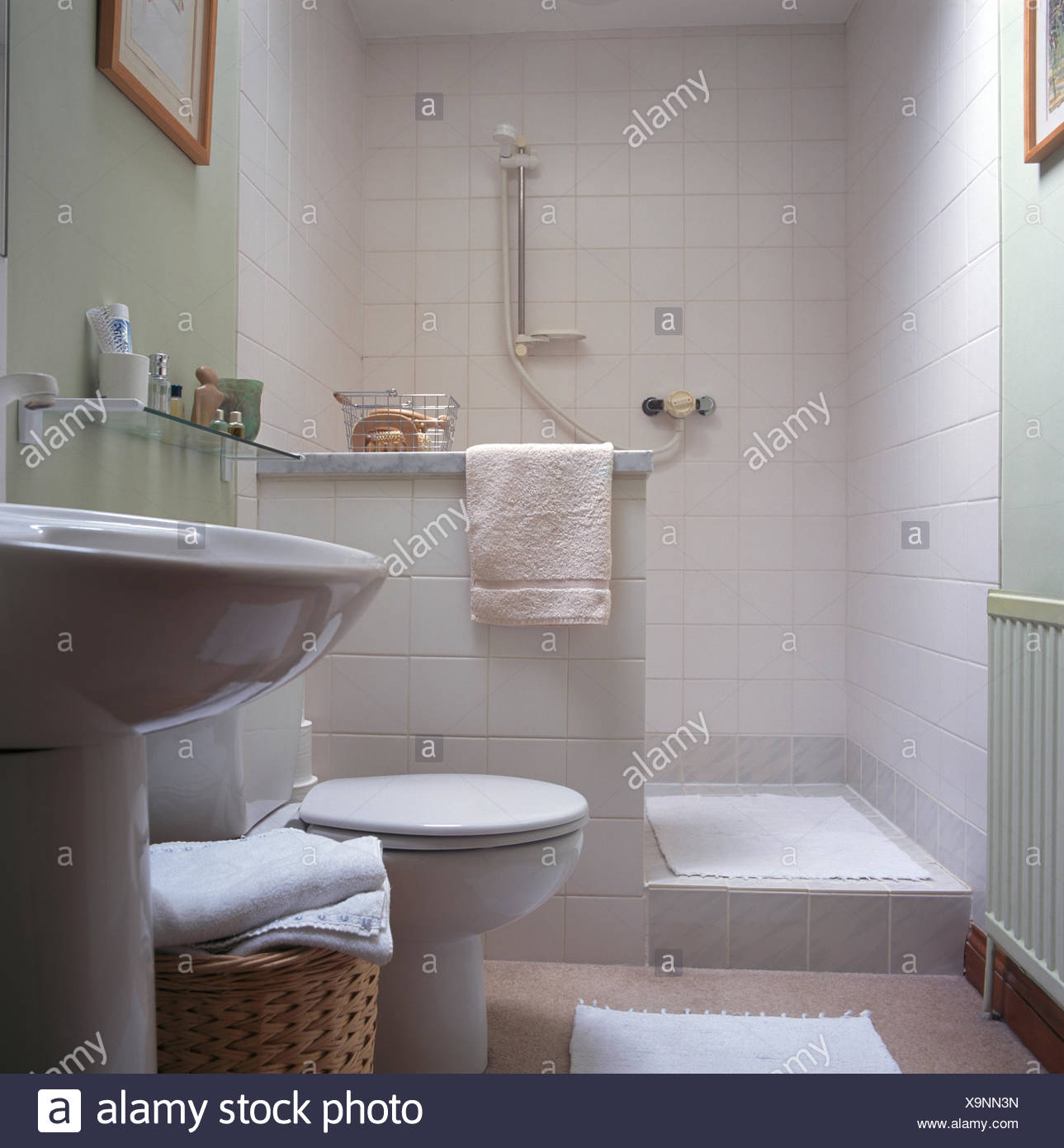 Walk-in white tiled shower in pale green bathroom with pedestal ...