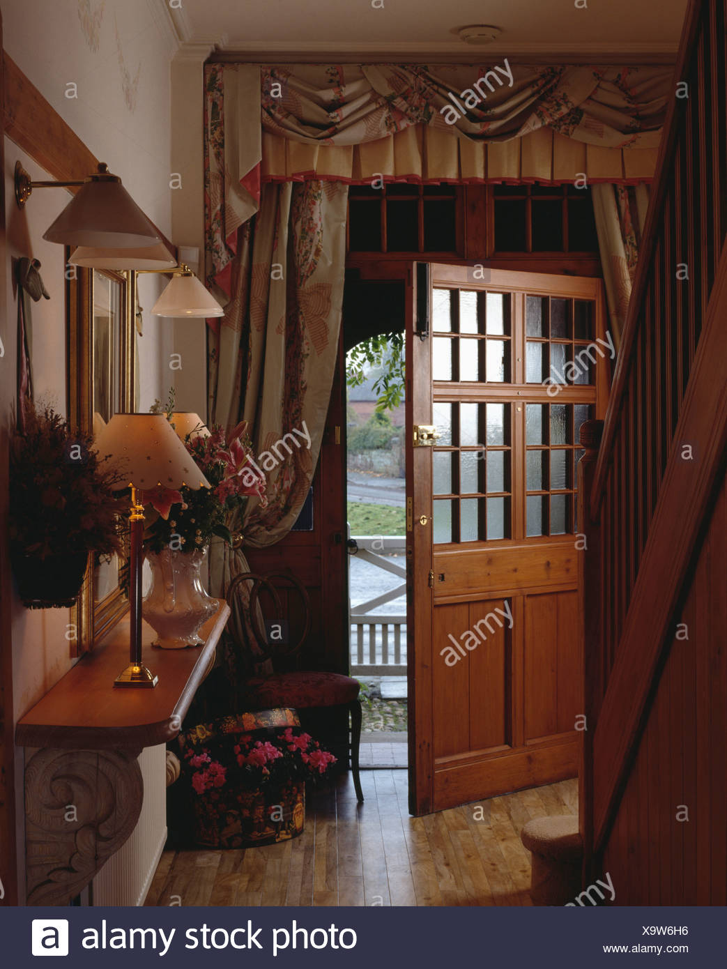 Opulent Curtains At Half Glazed Open Front Door In Country Hall With Lamps  On Console Table