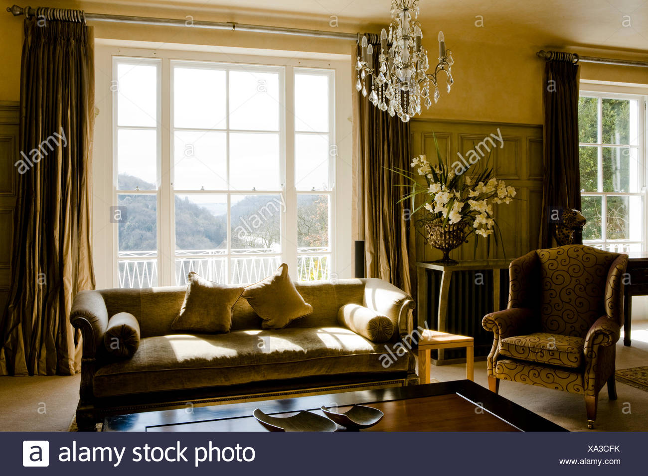 Awesome Beige Sofa And Patterned Armchair In Country Sitting Room With Silk Curtains