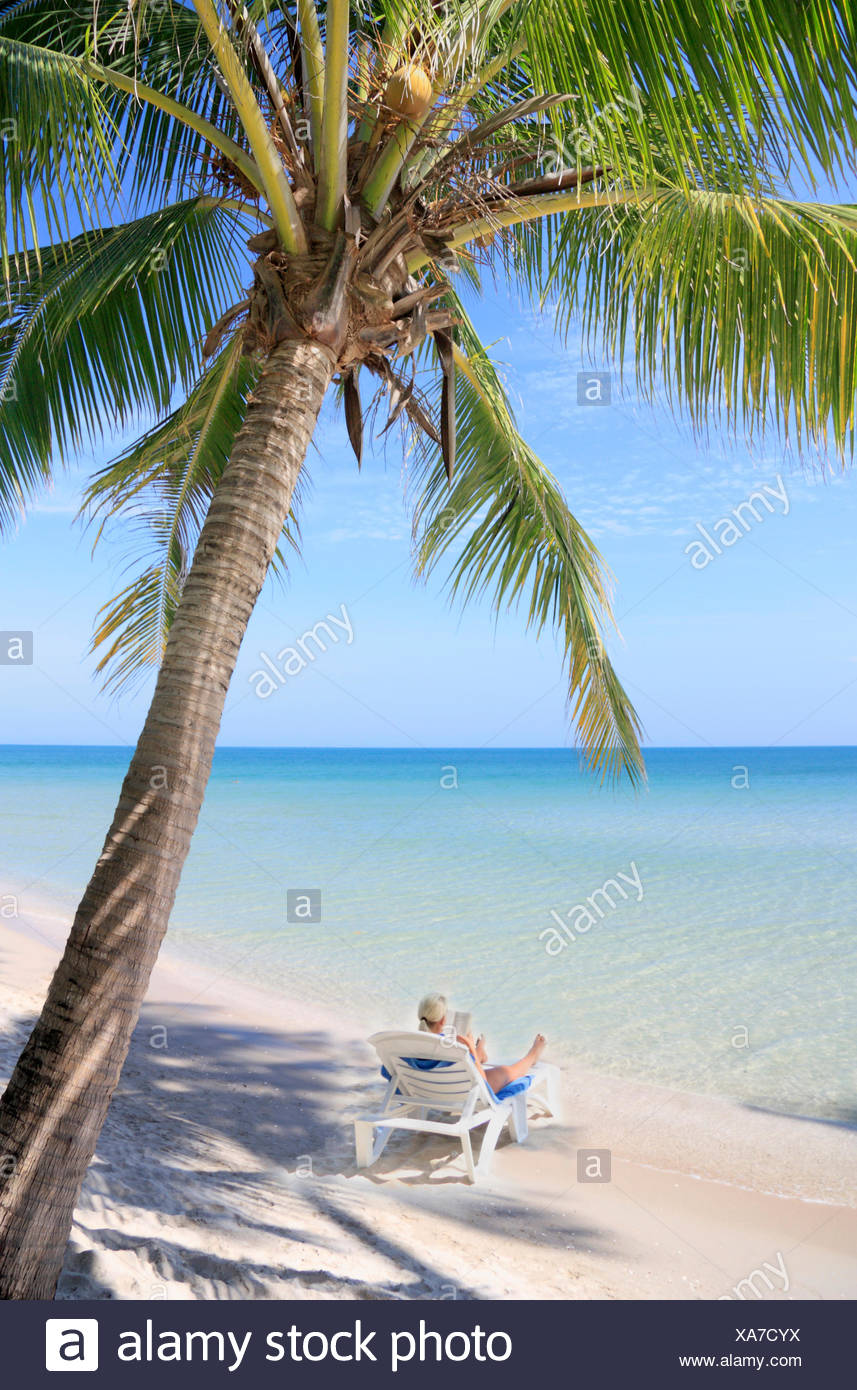 woman at the beach under a coconut tree thailand koh chang stock
