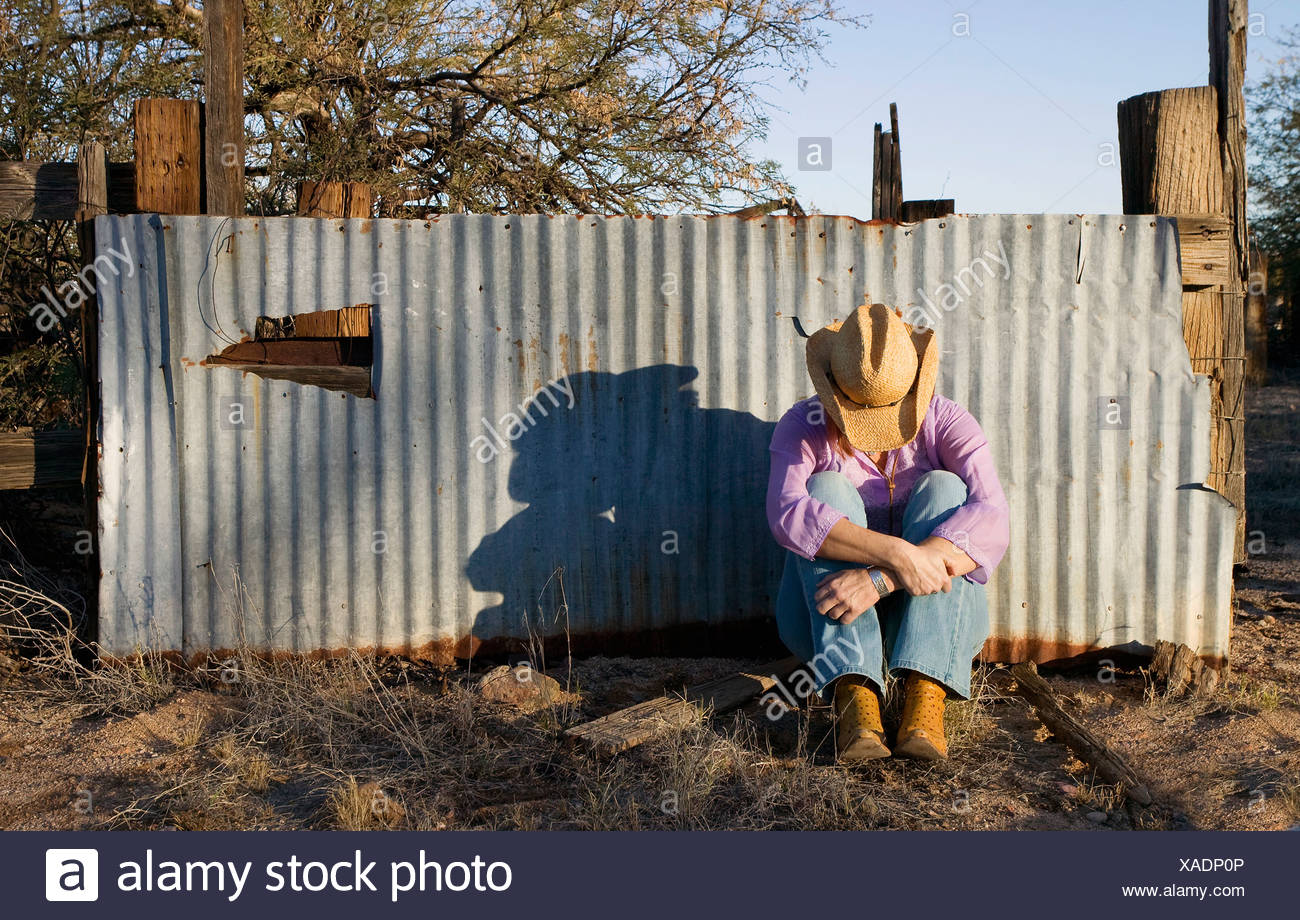2a949bc7d26 Woman wearing a straw cowboy hat with her head down leaning against a  corrugated metal fence.