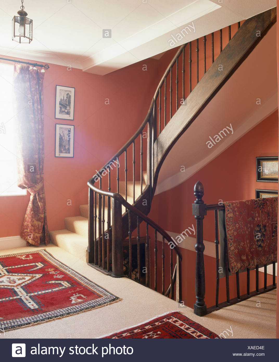 Dark Wood Banisters On Staircase In Red Landing With Persian Rugs On