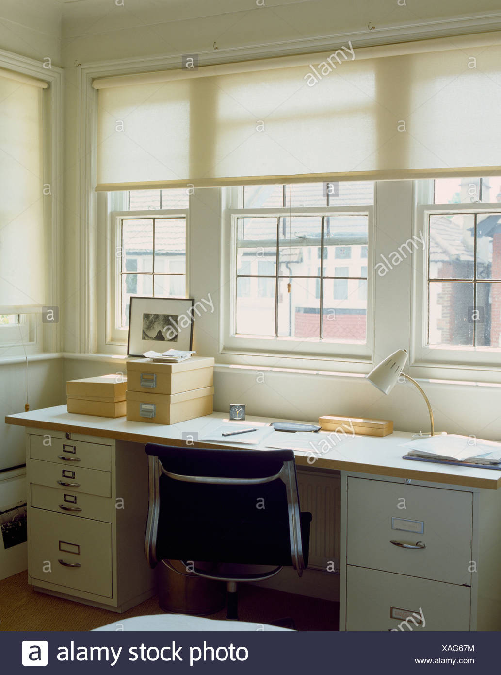 White Blinds At Window Above Black Chair And Desk With Storage Boxes And  Filing Cabinets In Home Office