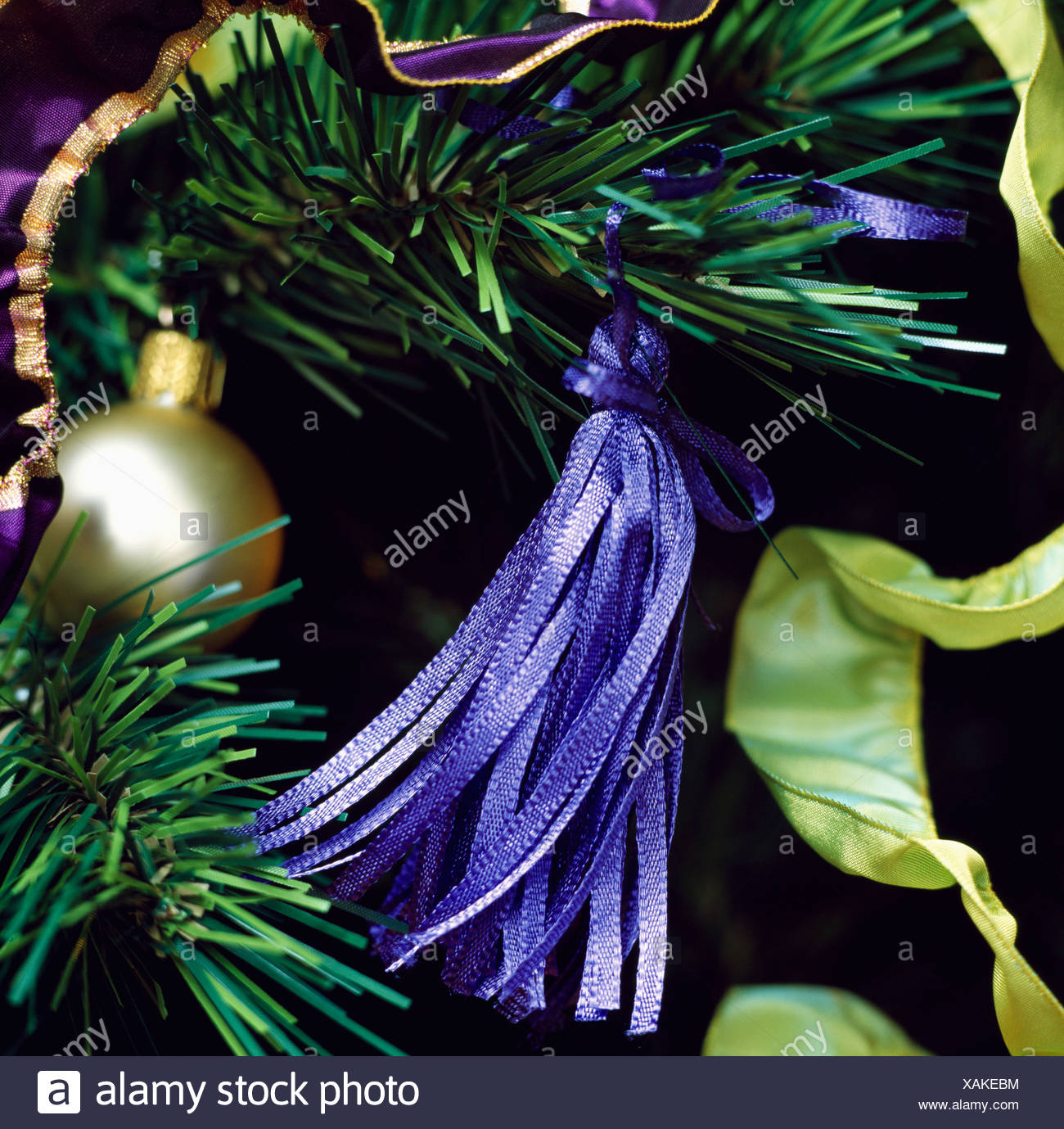 close up of blue silk tassel on faux christmas tree branch with gold bauble and lime green silk ribbon
