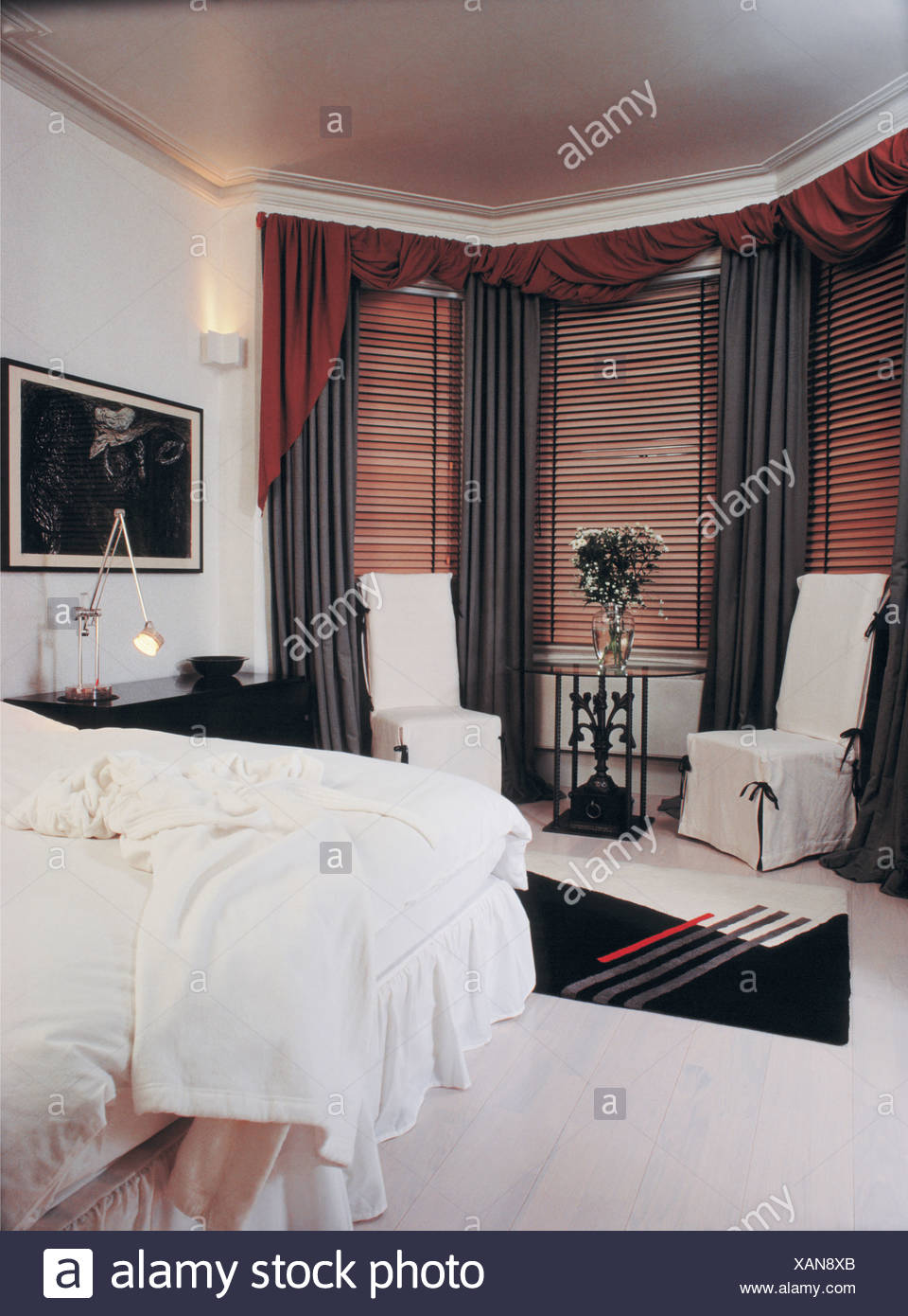 White Loosecovers On Chairs Beside Bay Window With Wooden Blinds And Black  Curtains In Bedroom With White Carpet And Bedlinen