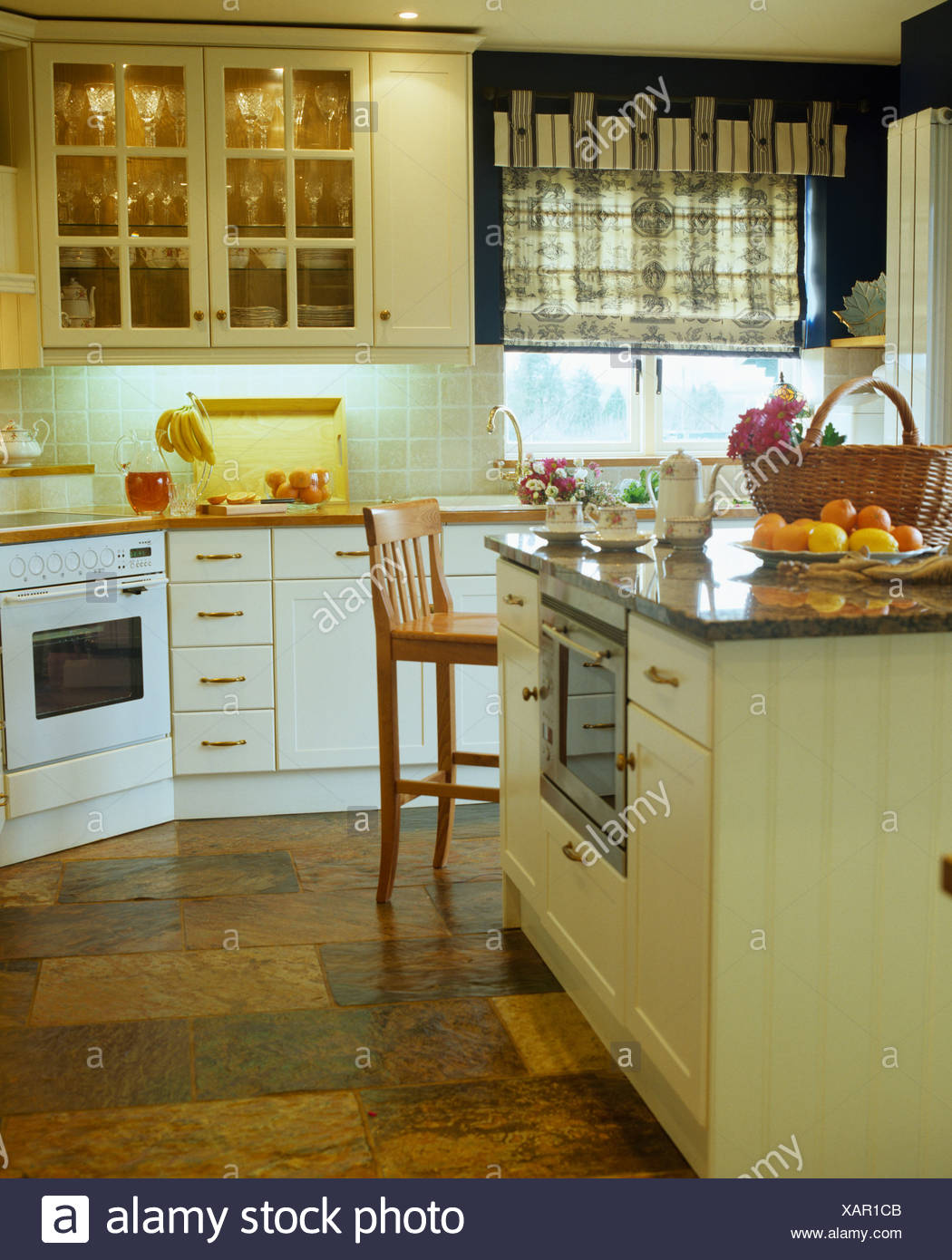 Island Unit And Slate Flooring In Country Kitchen With Patterned Blind On Window Beside Wall Cupboard Interior Lighting