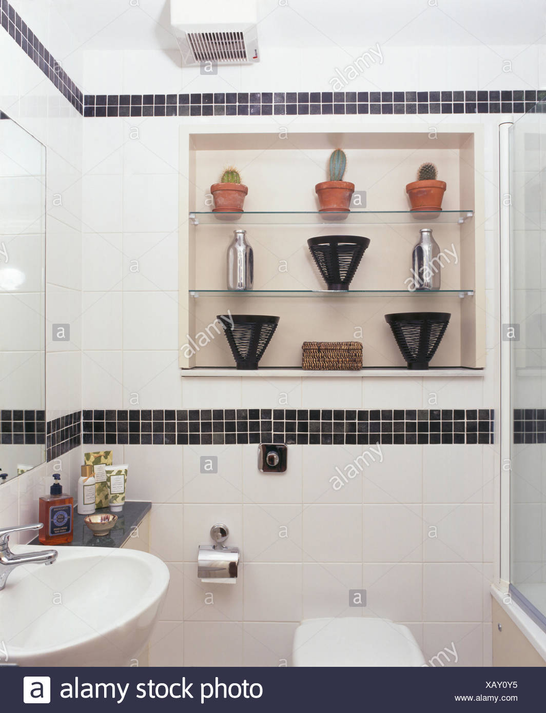 Black mosaic tiled border in modern white bathroom with glass ...