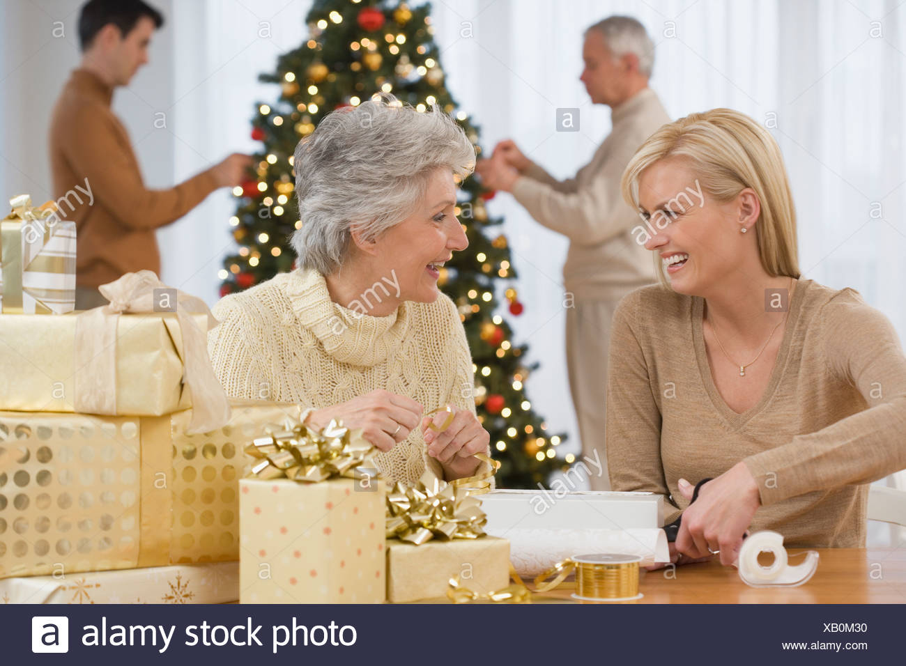 Mother and adult daughter wrapping Christmas gifts Stock Photo ...