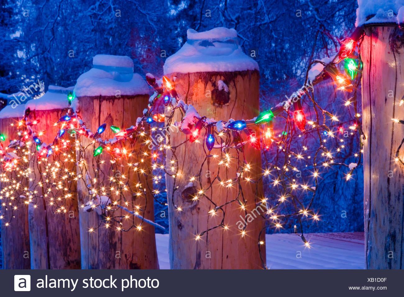 close up of christmas lights on log cabin porch railing at twilight near fairbanks alaska during winter