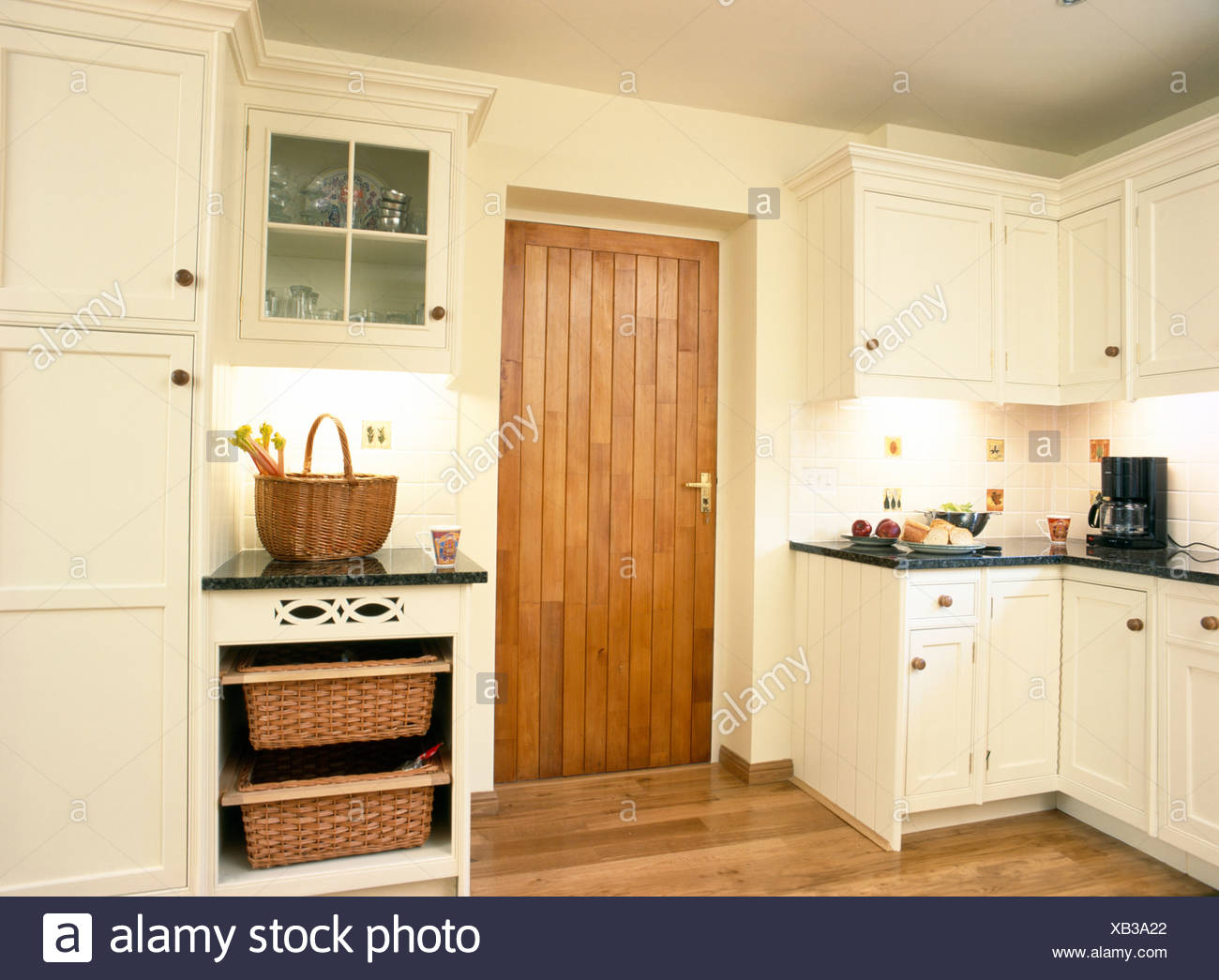 Delicieux Storage Baskets In Fitted Unit Beside Wooden Door In Cream Country Kitchen