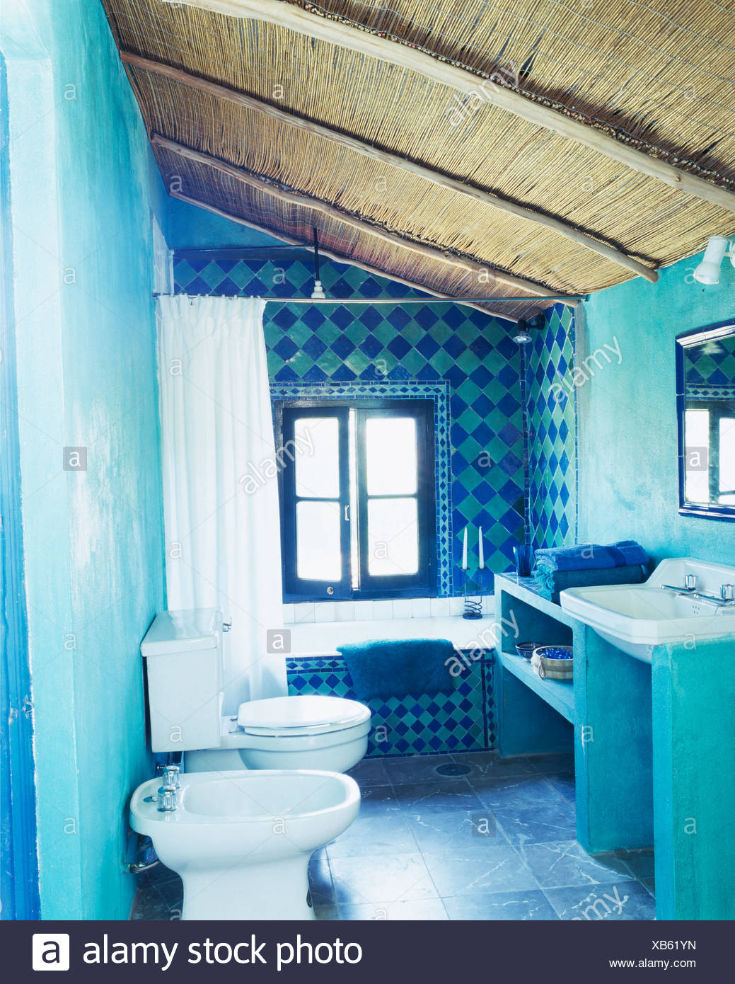 Thatched ceiling in turquoise Spanish bathroom with decorative blue+ ...