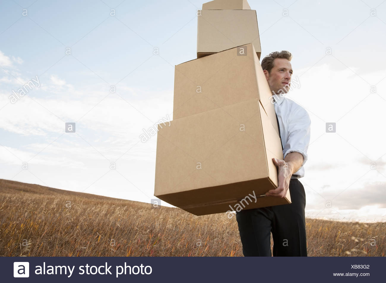 businessman carrying stacked boxes on field stock photo 282305522