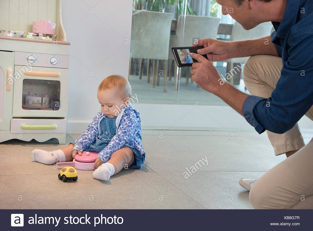 Mature man taking picture of her baby daughter playing with toys