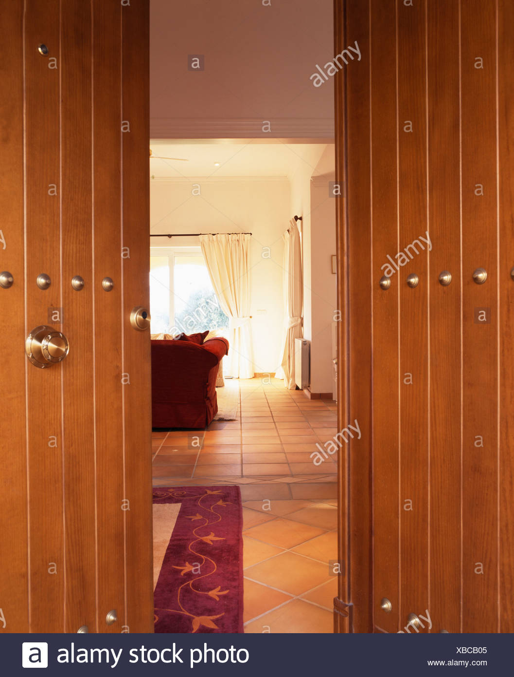 Double Wooden Doors Open To Hall In Spanish Villa Stock Photo