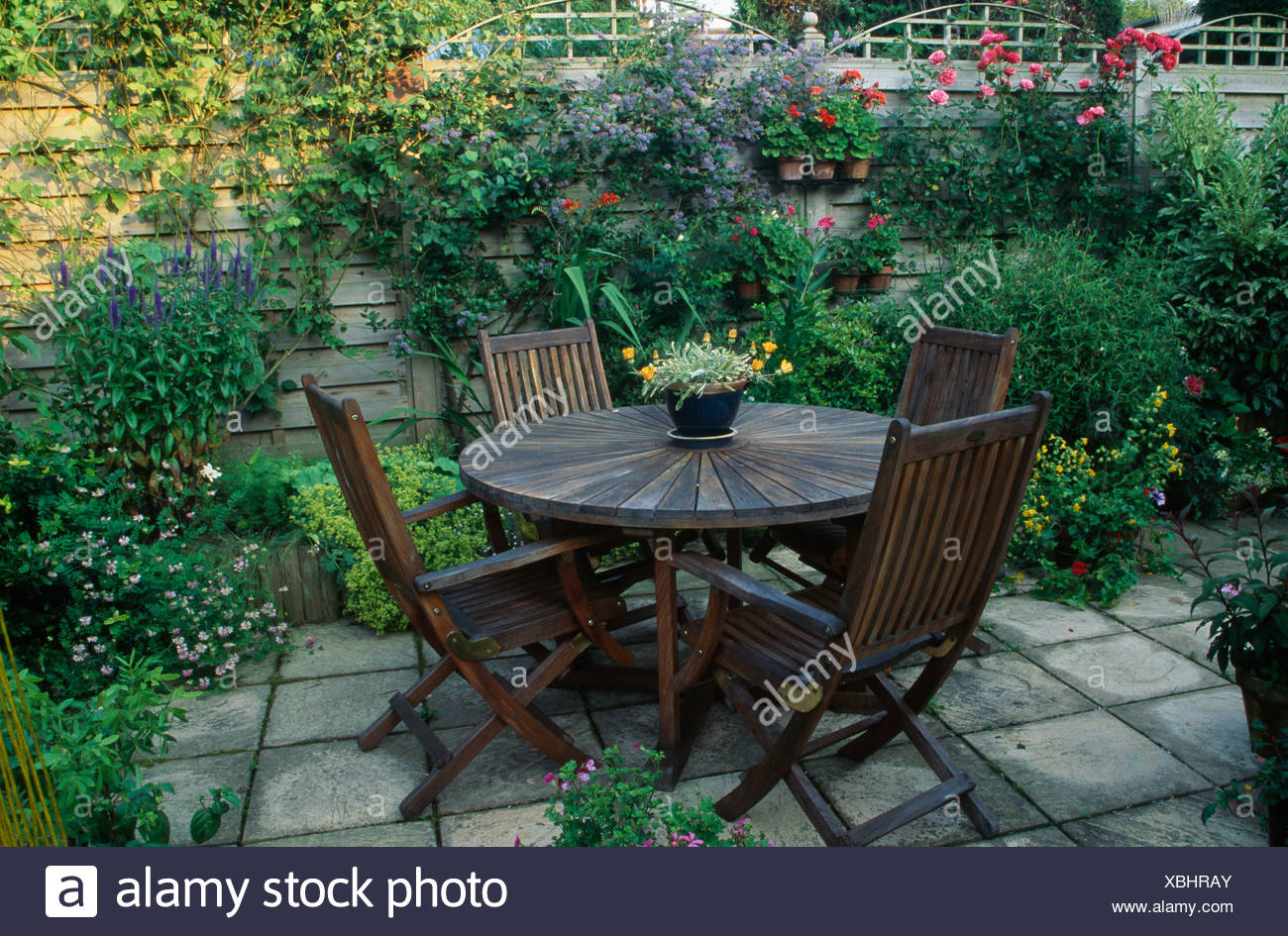Wooden Chairs And Circular Wooden Table On Paved Patio In Country Garden In  Summer With Pots Of Annuals On Wooden Fence