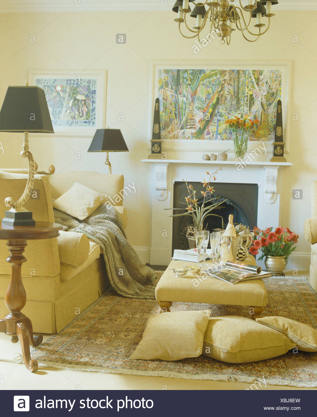 Pale Yellow Cushions On Floors Beside Upholstered Stool In Living Room With  Pale Yellow Sofas And Black Lamp On Tripod Table